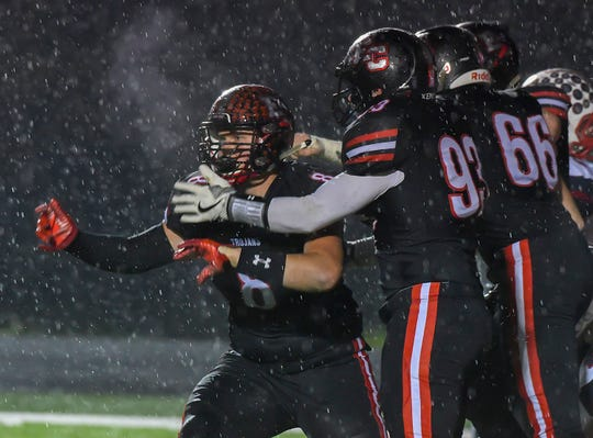 East Central linebacker Brett Fox (left) celebrates a quarterback sack against S. Dearborn in the IHSAA playoffs at East Central High School, Friday, Oct. 26, 2018, St. Leon, IN