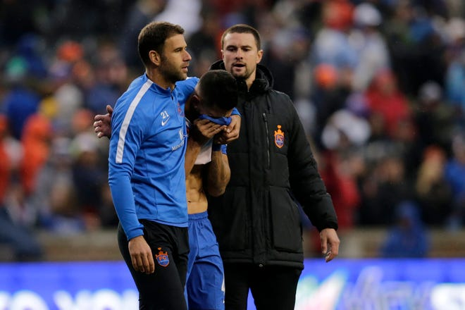 FC Cincinnati defender Dekel Keinan (21) and strength coach Austin Berry walk midfielder Emmanuel Ledesma (45) off the field after the second half of the USL Eastern Conference Semifinal match between the FC Cincinnati and the New York Red Bulls II at Nippert Stadium in Cincinnati on Tuesday, Oct. 16, 2018. FC Cincinnati was eliminated from the playoffs with a 1-0 loss to New York.