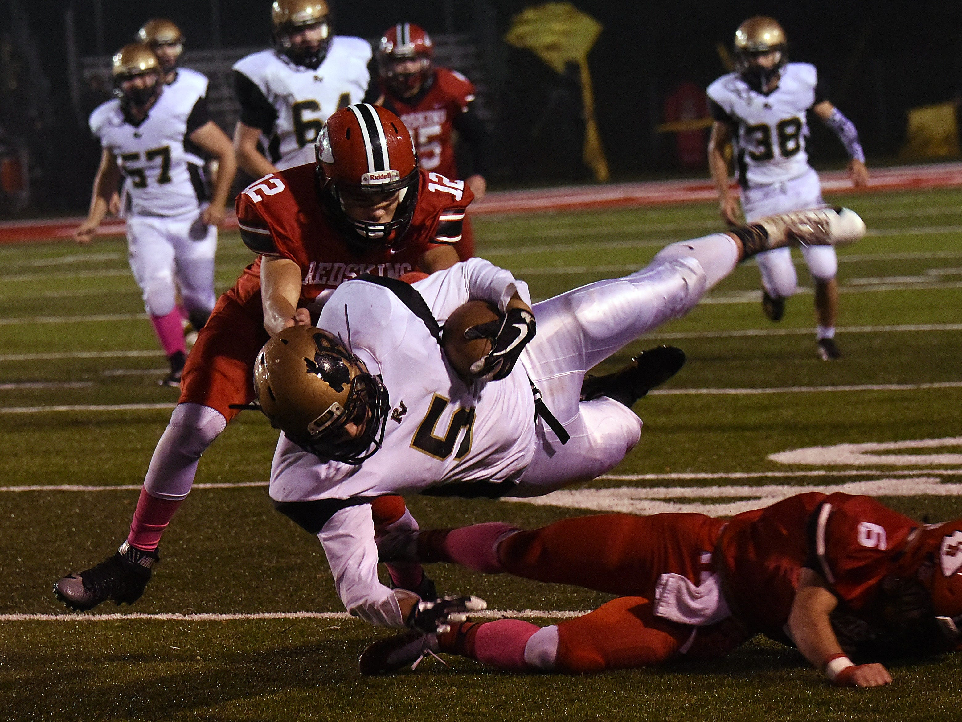 Coshocton freshman Isaac Shook (left) and senior Andrew Kittell (right) bring down River View ball carrier senior Eric Jacobs. Coshocton defeated the Bears 29-14 on Friday, Oct. 26, 2018.
