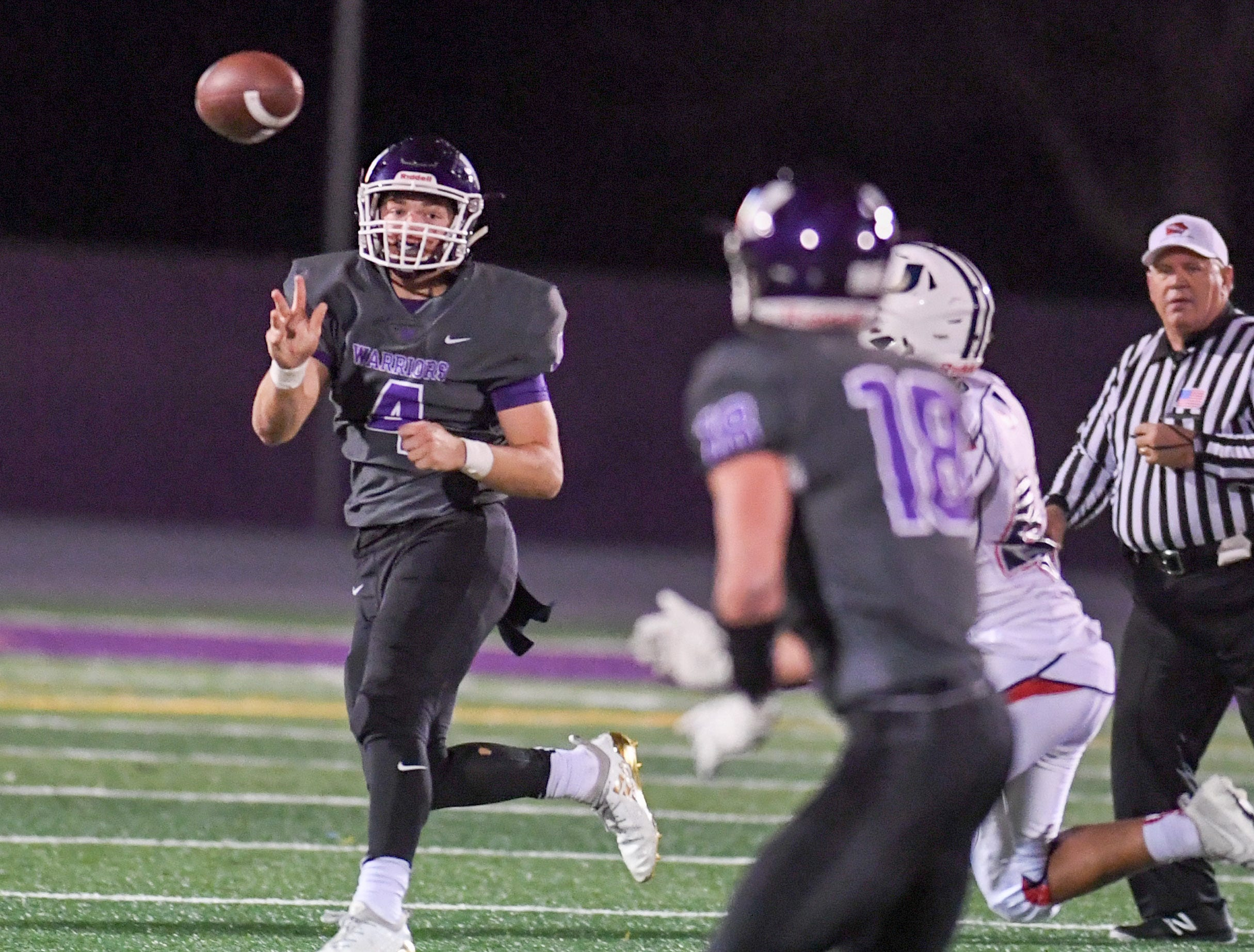 Waukee Quarterback Mitch Randall (4) makes a pass to Zach Eaton (18) on Friday, Oct. 26, 2018 during a playoff game between the Waukee Warriors and the Urbandale J-Hawks at Waukee High School.