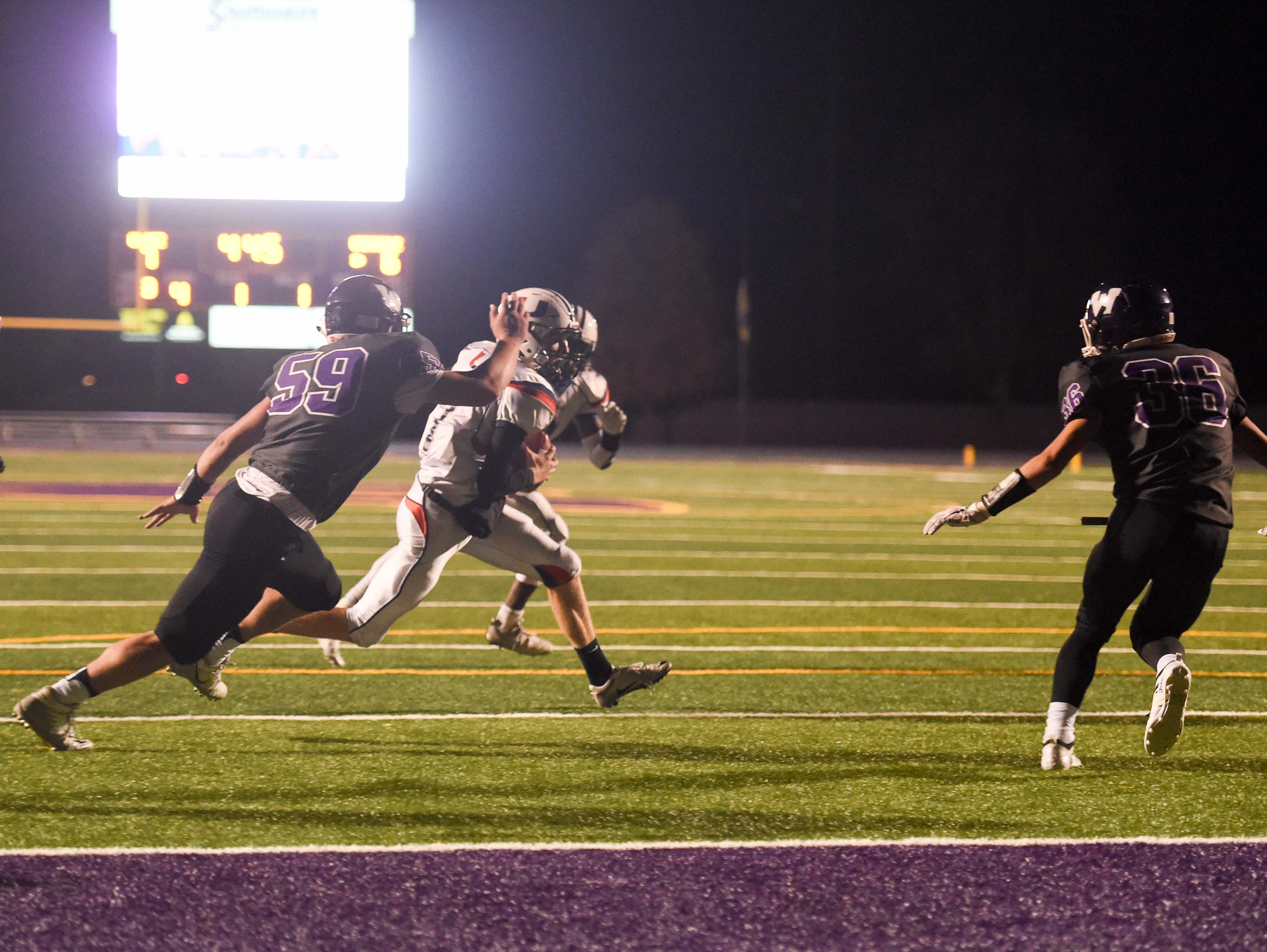 Urbandale quarterback Ty Langenberg (7) runs the ball for th the endzone on Friday, Oct. 26, 2018 during a playoff game between the Waukee Warriors and the Urbandale J-Hawks at Waukee High School.