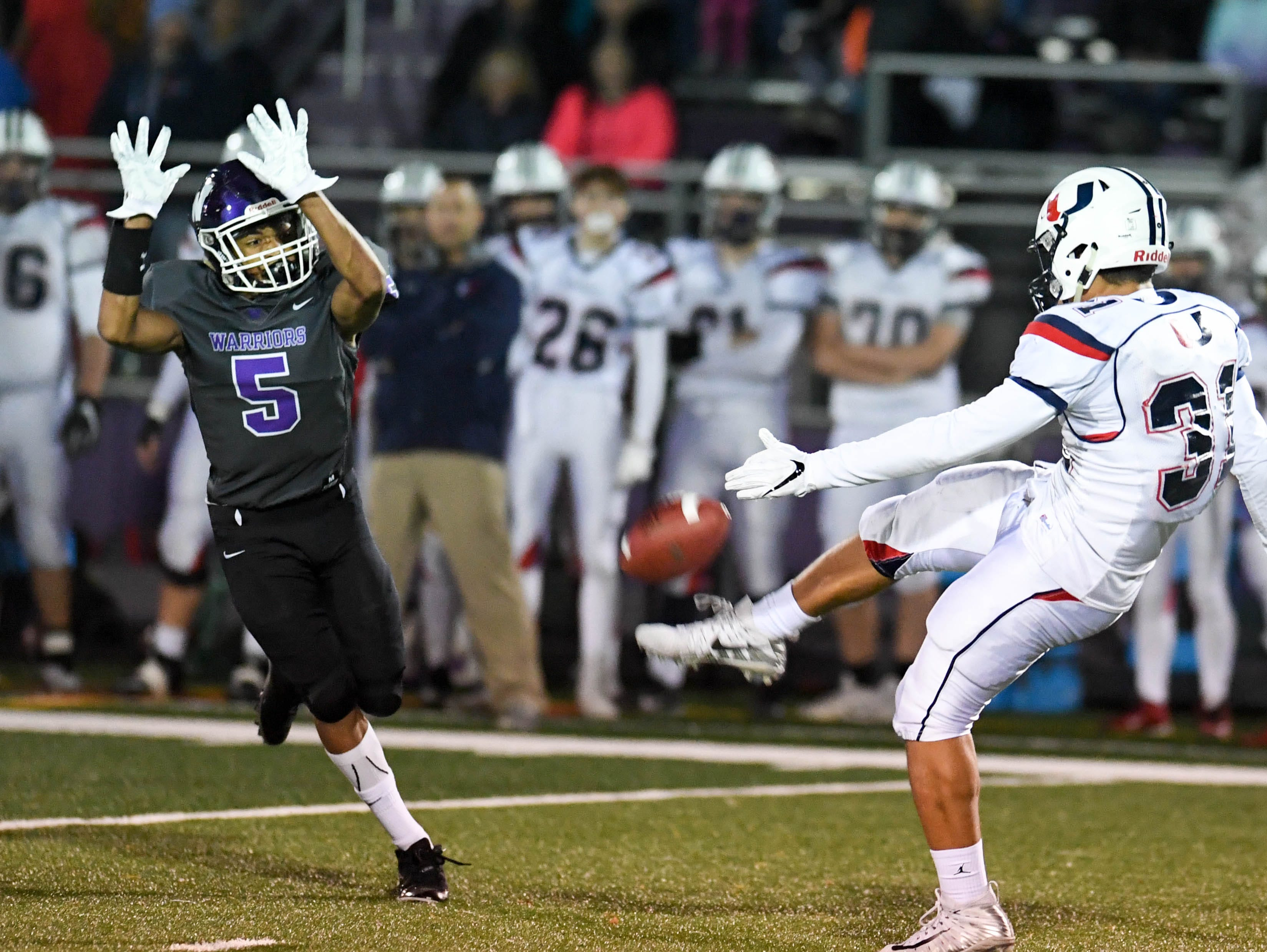 Urbandale's Jacob Brechtel (33) tries to get the punt away under preasure from Waukee's Aaron Smith (5) on Friday, Oct. 26, 2018 during a playoff game between the Waukee Warriors and the Urbandale J-Hawks at Waukee High School.