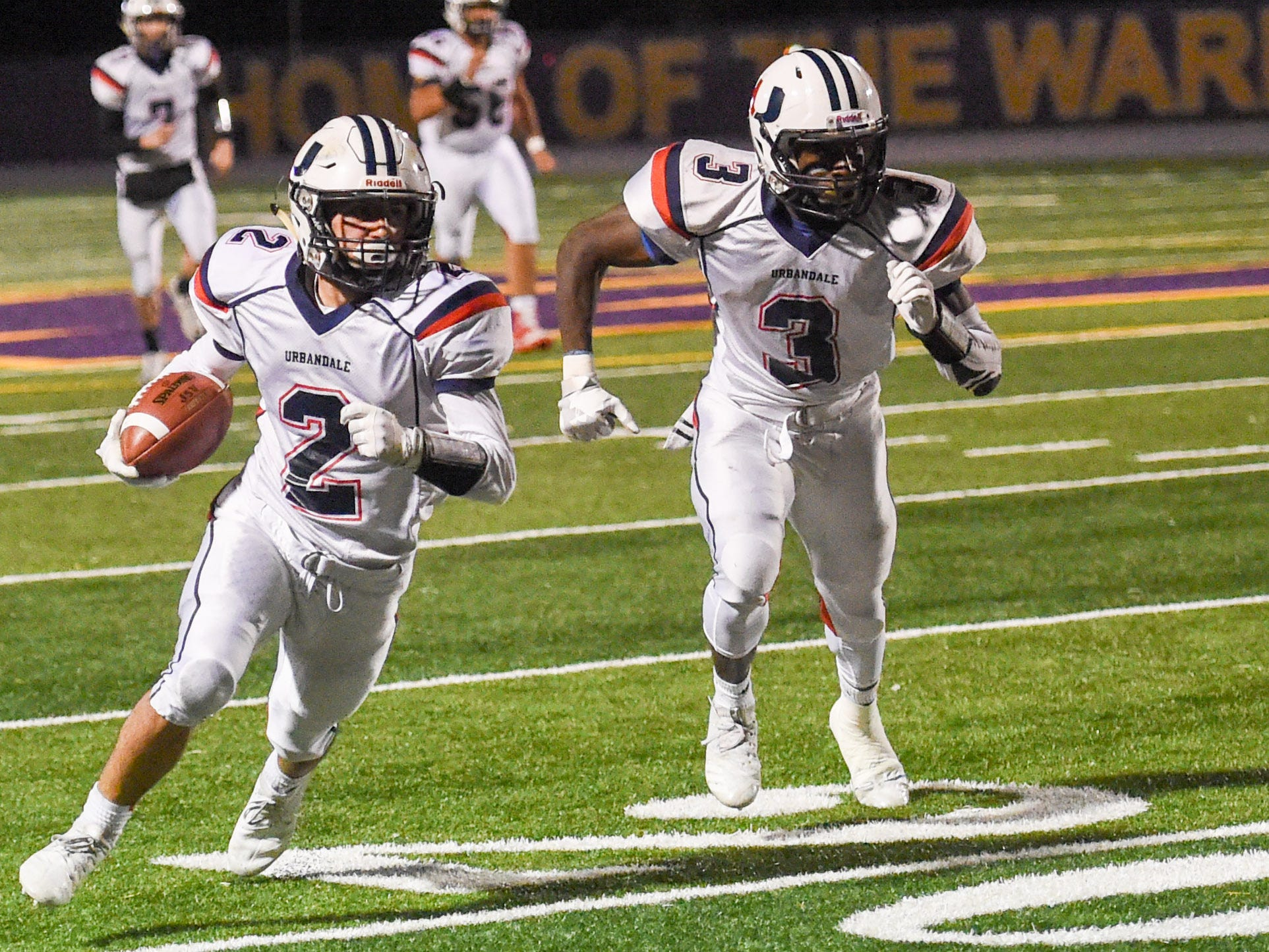 Urbandale's Alex Economos (2) runs the ball as Harrison Waylee (3) blocks on Friday, Oct. 26, 2018 during a playoff game between the Waukee Warriors and the Urbandale J-Hawks at Waukee High School.