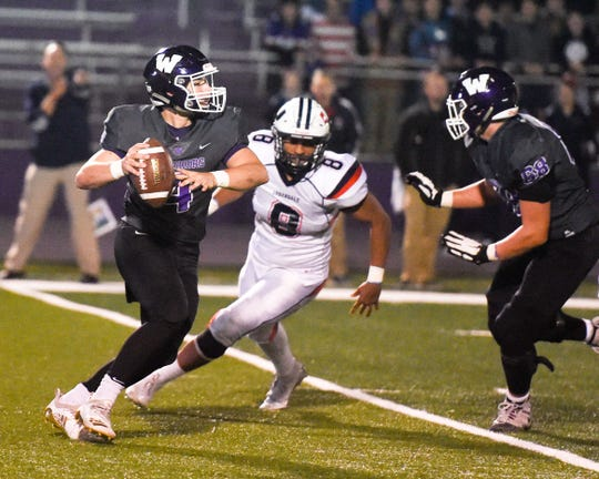 Urbandale's Riley Longlet (8) puts pressure on Waukee quarterback Mitch Randall (4) on Friday, Oct. 26, 2018 during a playoff game between the Waukee Warriors and the Urbandale J-Hawks at Waukee High School.