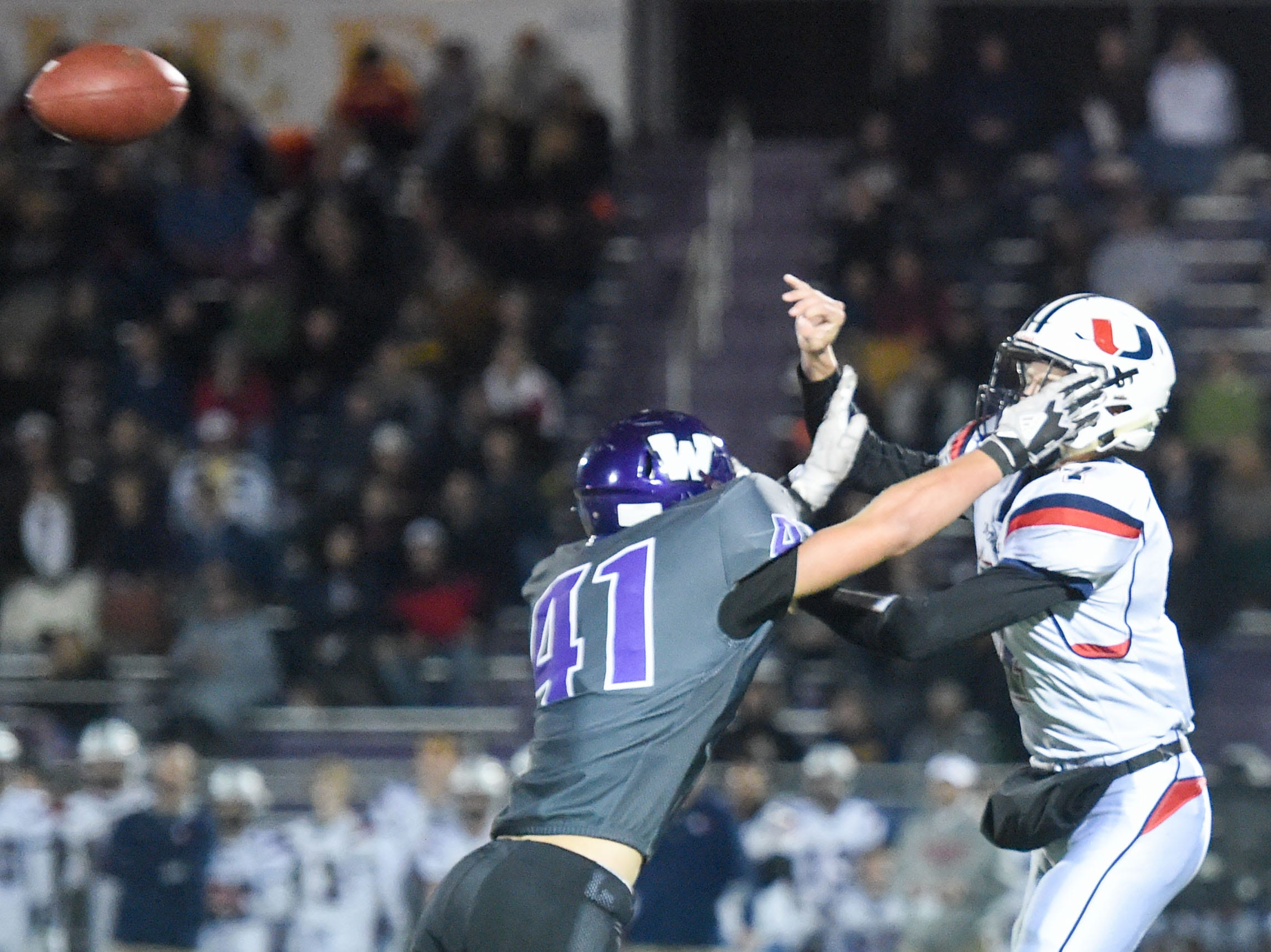 Urbandale quarterback Ty Langenberg (7) makes a quick pass while under pressure from Waukee's Cole Spyksma (41) on Friday, Oct. 26, 2018 during a playoff game between the Waukee Warriors and the Urbandale J-Hawks at Waukee High School.