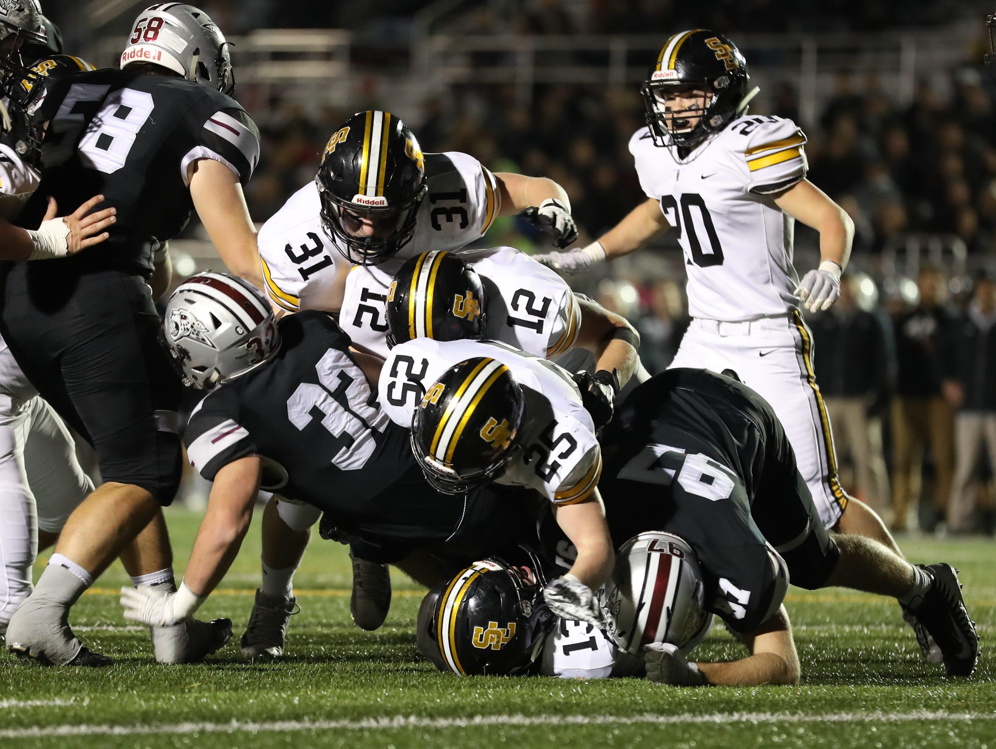 Ankeny Centennial Jaguars Gabe Godwin (32) is tackled by Southeast Polk Rams Jacob Robillard (13) and Southeast Polk Rams Zach Strickland (25) at Ankeny football stadium.