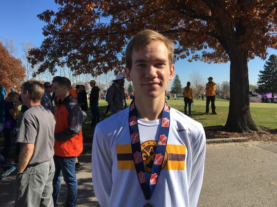 Ankeny senior Tim Sindt poses with his first-place medal at the Iowa state cross country meet.