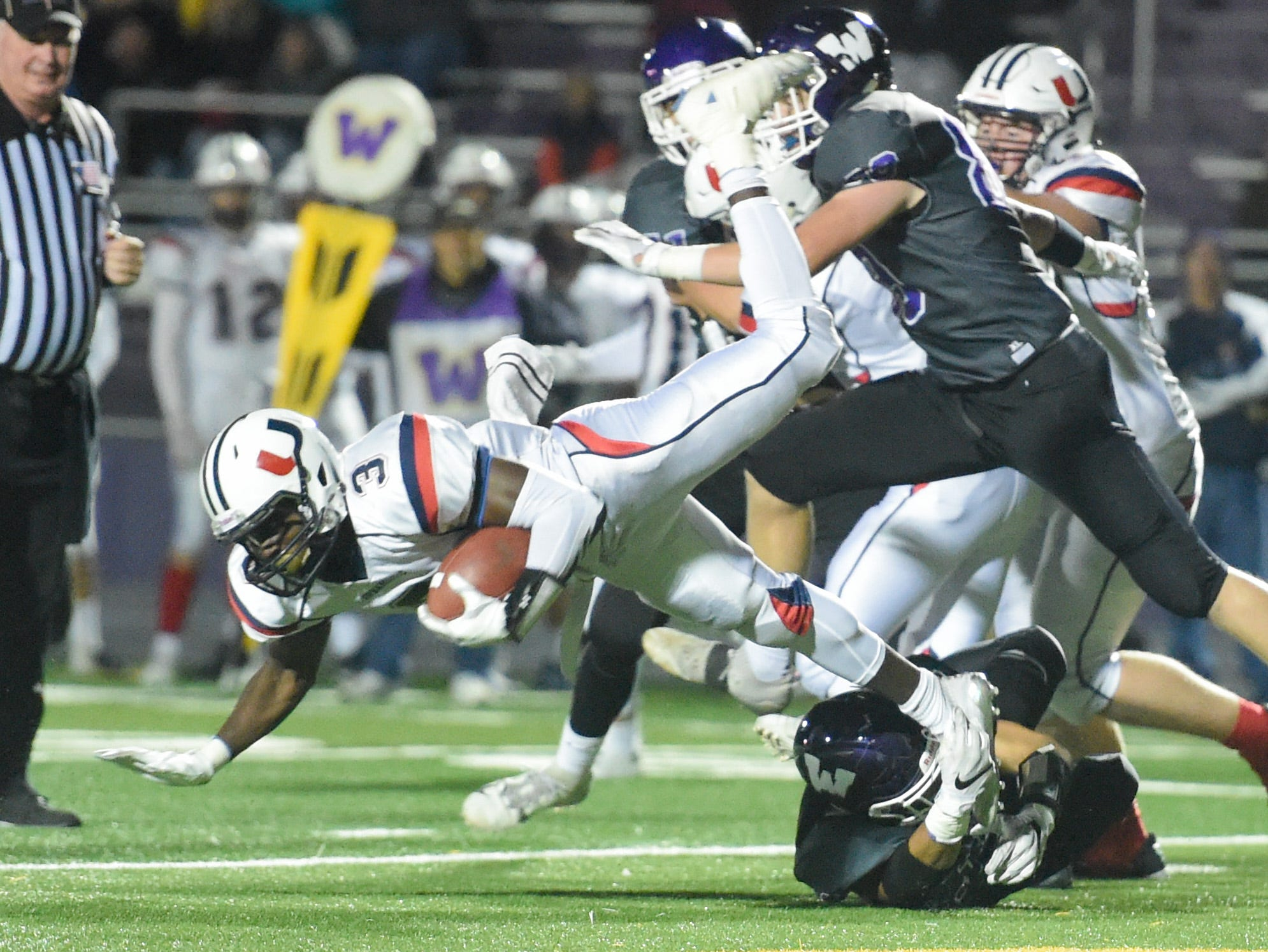 Urbandale's Harrison Waylee (3) fights past Waukee defenders on Friday, Oct. 26, 2018 during a playoff game between the Waukee Warriors and the Urbandale J-Hawks at Waukee High School.
