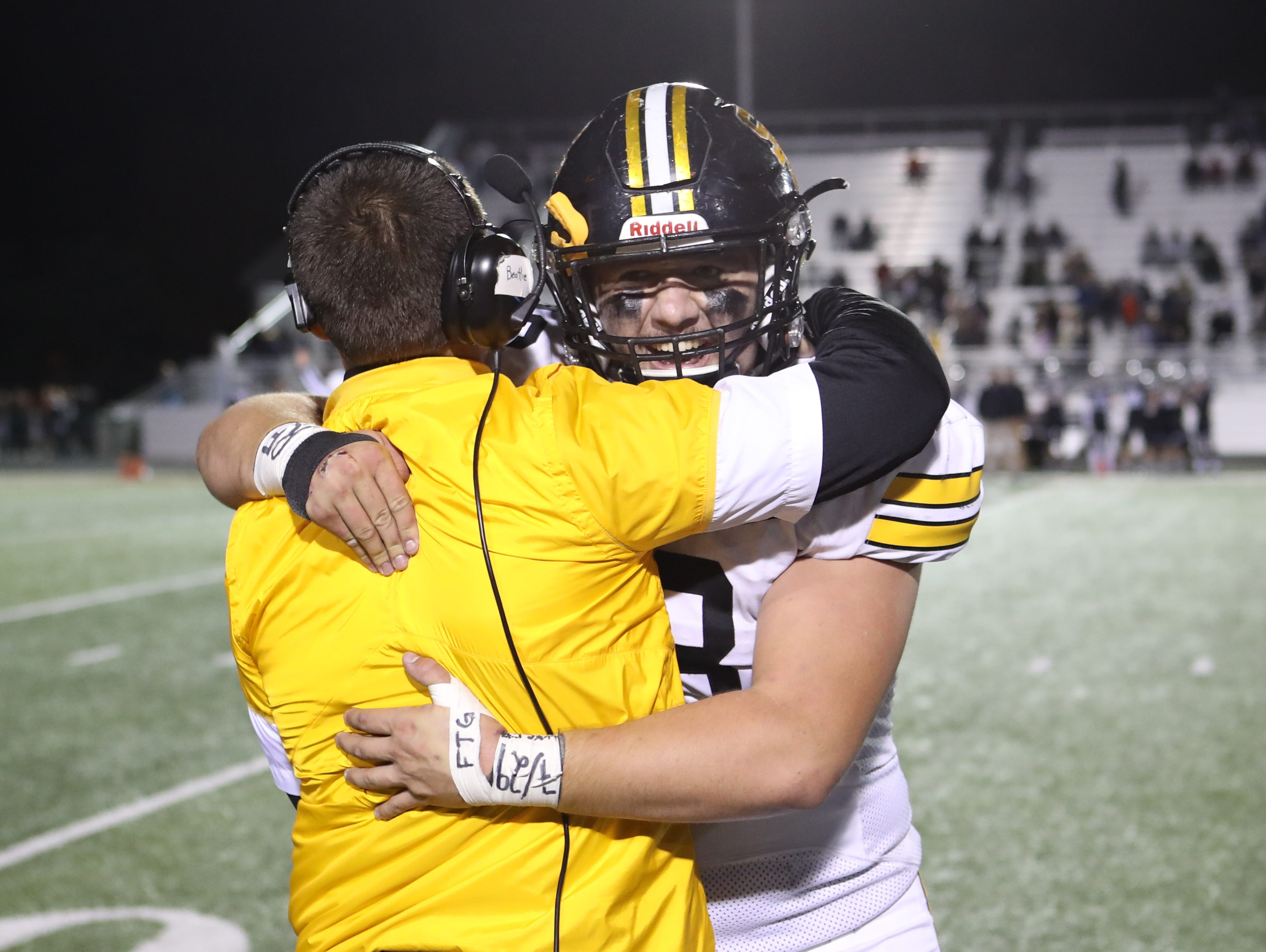 Southeast Polk Rams Bo Ira (48) celebrates the win with Southeast Coach Assistant Coach Luke VanderSanden against the Ankeny Centennial Jaguars at Ankeny football stadium . Mandatory Credit: Reese Strickland-for the register