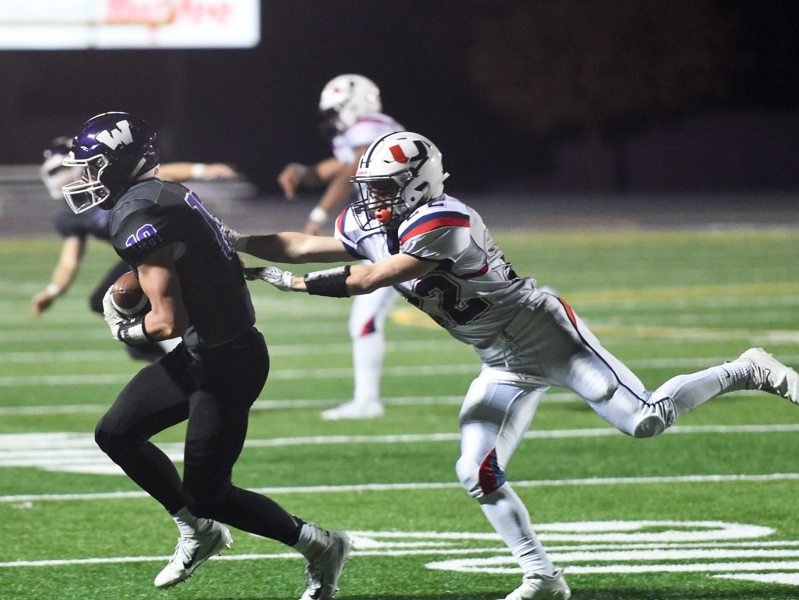 Urbandale's Brook Heinen (22) fights to tackle Waukee's Zach Eaton (18) on Friday, Oct. 26, 2018 during a playoff game between the Waukee Warriors and the Urbandale J-Hawks at Waukee High School.