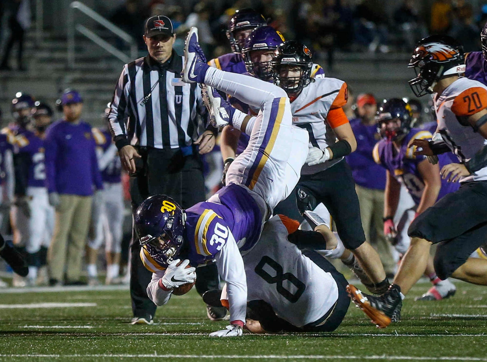 Johnston running back Nuutele Davis reaches for extra yards after being tackled by Cedar Rapids Prairie's Hunter Williams during the first round of Iowa high school football playoffs on Friday, Oct. 26, 2018.