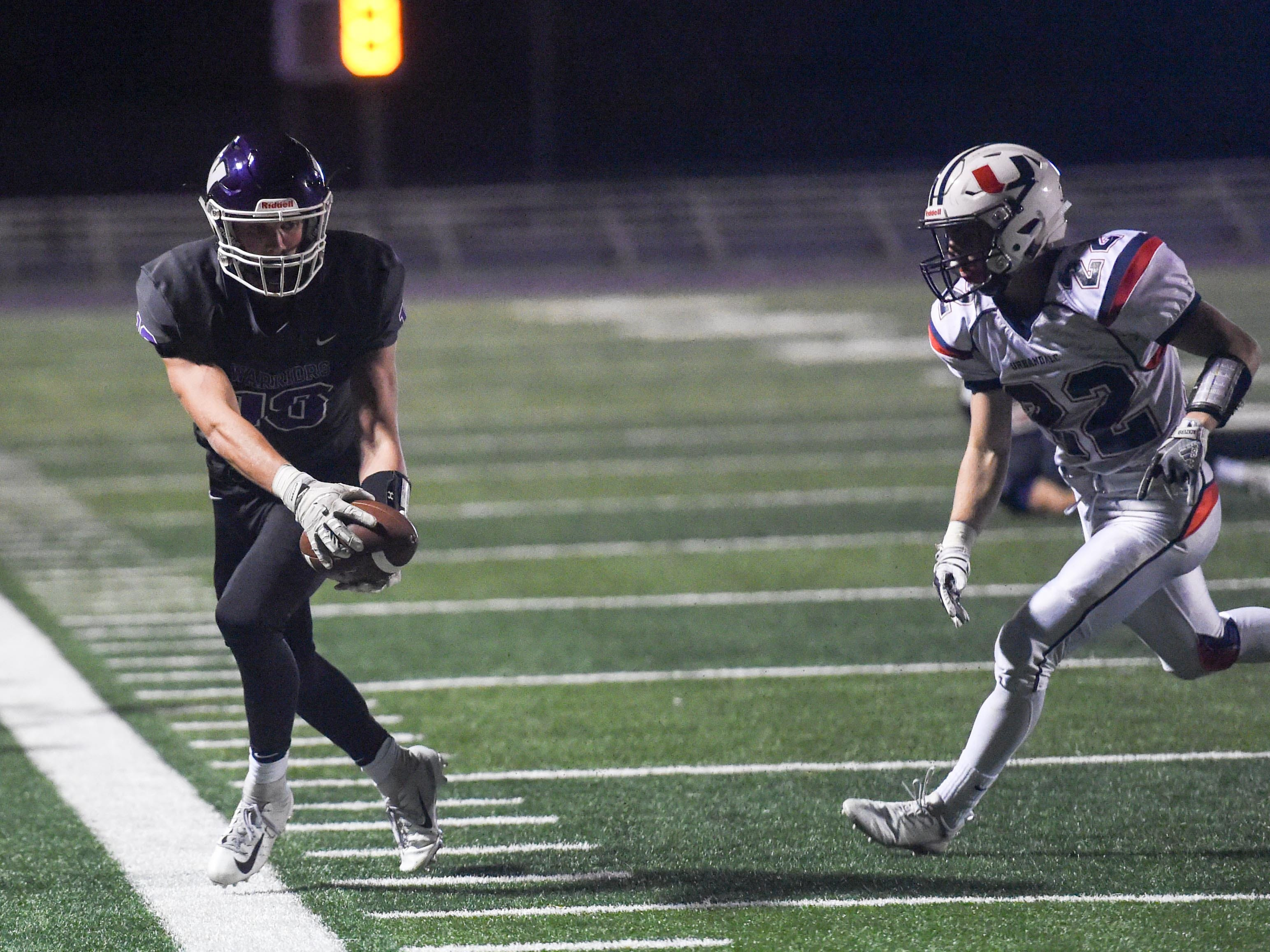 Urbandale's Brook Heinen (22) trails Waukee's Zach Eaton (18) as he makes a catch near the sideline on Friday, Oct. 26, 2018 during a playoff game between the Waukee Warriors and the Urbandale J-Hawks at Waukee High School.