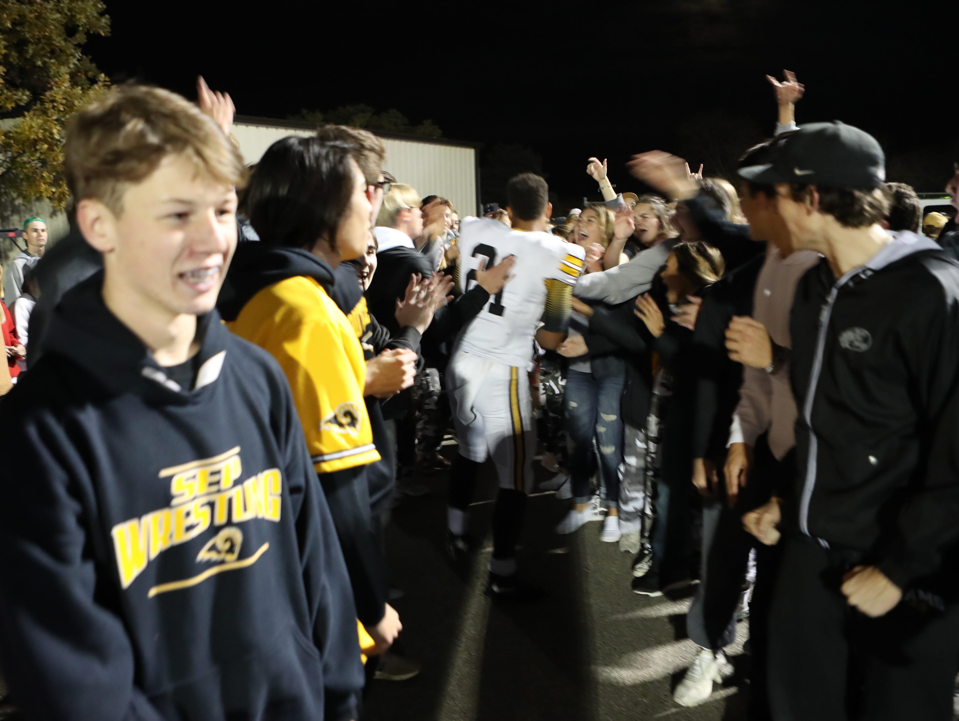 Southeast Polk Rams Gavin Williams (21) walks through happy fans after the Rams beat the Ankeny Centennial Jaguars at Ankeny football stadium.
