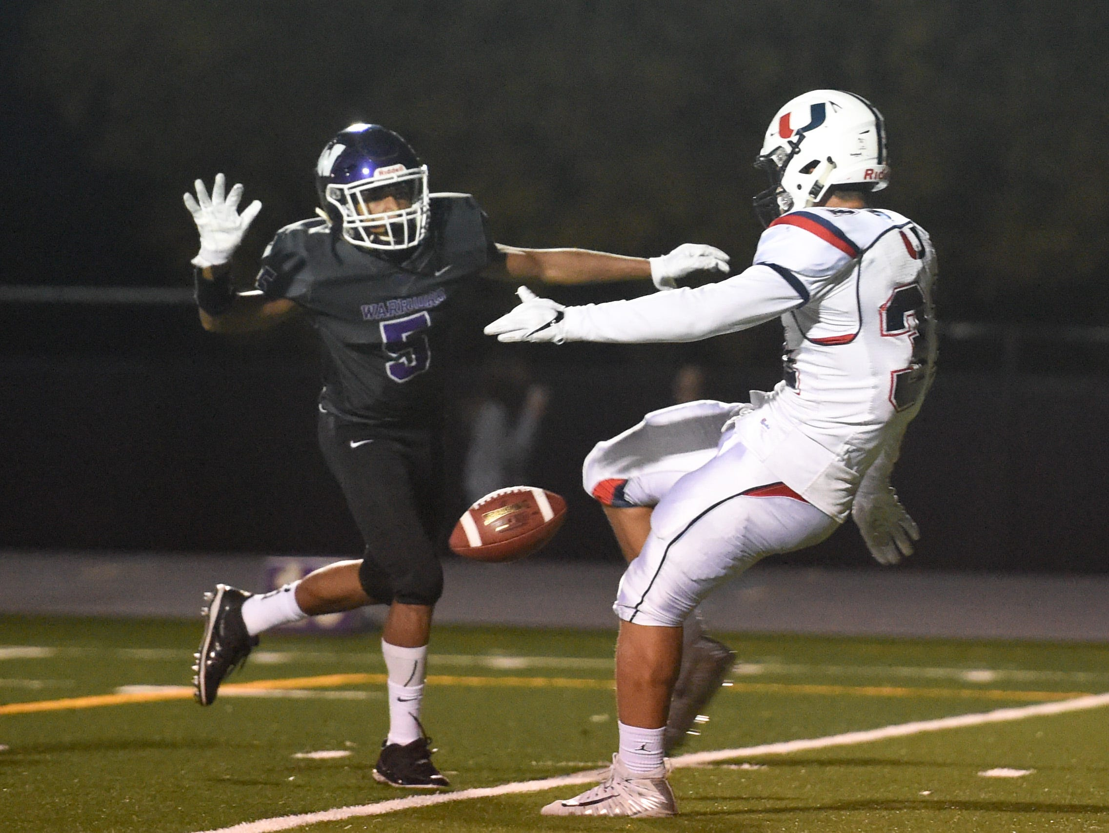 Urbandale's Jacob Brechtel (33) tries to get a punt away under pressure from Waukee's Aaron Smith (5) on Friday, Oct. 26, 2018 during a playoff game between the Waukee Warriors and the Urbandale J-Hawks at Waukee High School.