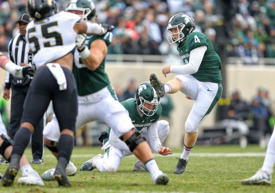 Michigan State  kicker Matt Coghlin (4) kicks a field goal out of the hold of Spartans quarterback Brian Lewerke (14) during the first quarter of a game at Spartan Stadium.