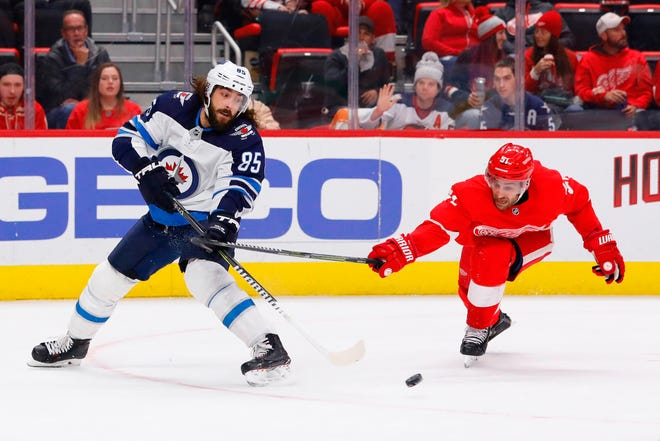 Winnipeg Jets left wing Mathieu Perreault skates with the puck, chased by Detroit Red Wings center Frans Nielsen in the first period at Little Caesars Arena on Oct. 26, 2018 in Detroit.