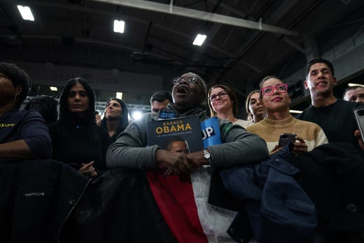 People watch as the 44th United States President Barack Obama speaks during Michigan's departure of the Michigan Democratic Party Rally on Friday, October 26, 2018 at Detroit Cass Tech High School ,
