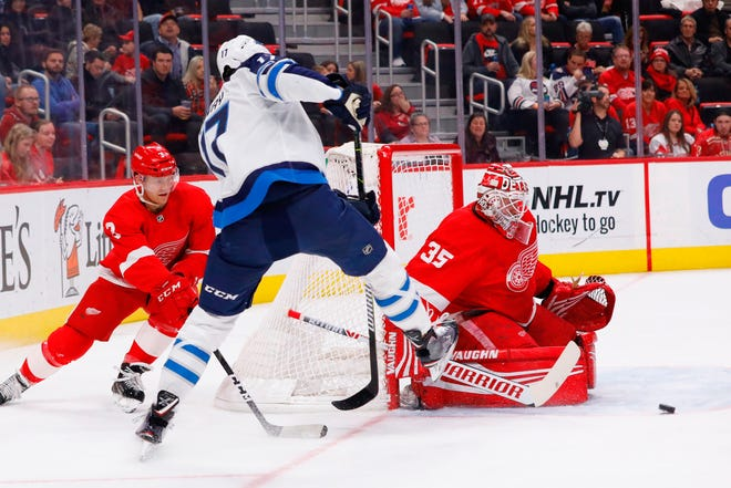 Detroit Red Wings goaltender Jimmy Howard makes the save on Winnipeg Jets center Adam Lowry in the first period at Little Caesars Arena on Oct. 26, 2018 in Detroit.