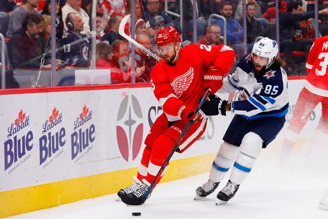 Detroit Red Wings defenseman Mike Green gets to the puck before Winnipeg Jets left wing Mathieu Perreault in the first period at Little Caesars Arena on Oct. 26, 2018 in Detroit.
