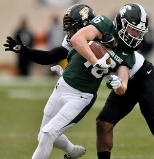 Michigan State's Brandon Sowards twists through the grip of Purdue's Simeon Smiley in the first quarter.