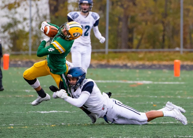 John Wright (4) of Farmington Hills Harrison makes a midfield catch and is tackled by Kobi Russel (1) of Cranbrook Kingswood in the first half.