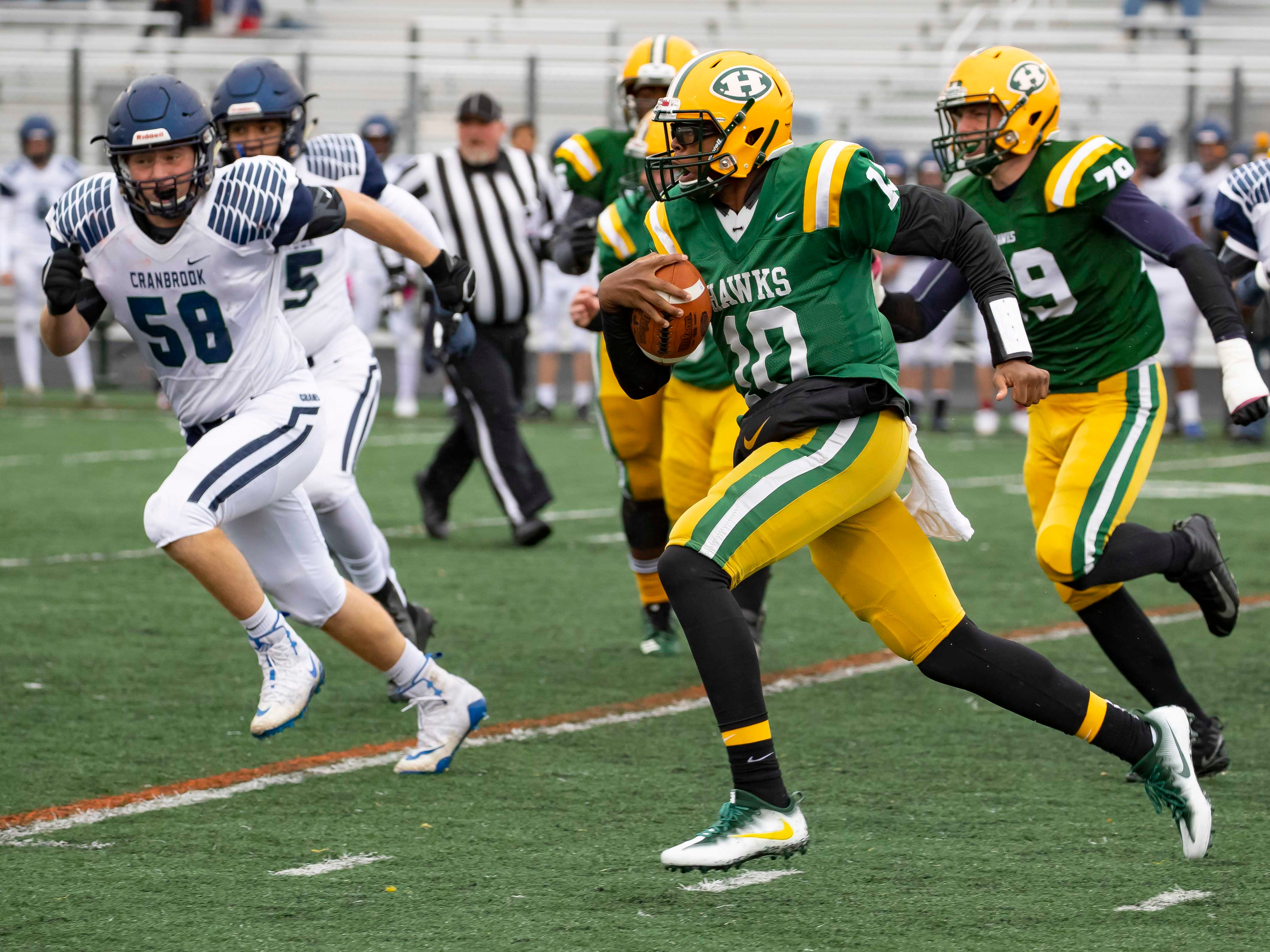 Keel Watson (10) of the Farmington Hills Harrison Hawks runs the with the football as William Kerr (58) of Cranbrook Kingswood pursues in the first half.