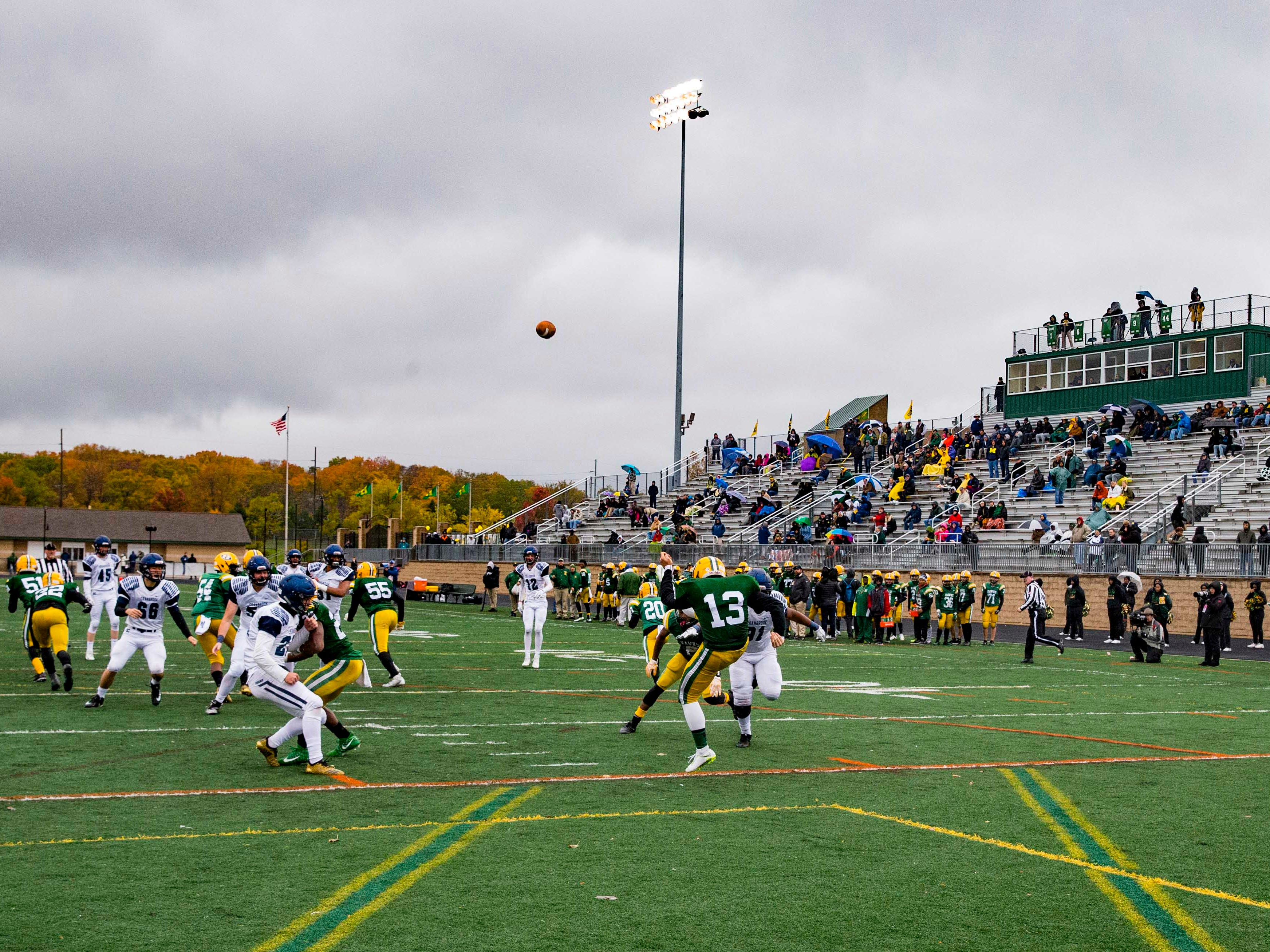 David Hiser (13) of Farmington Hills Harrison punts the ball in the first half against Cranbrook Kingswood.