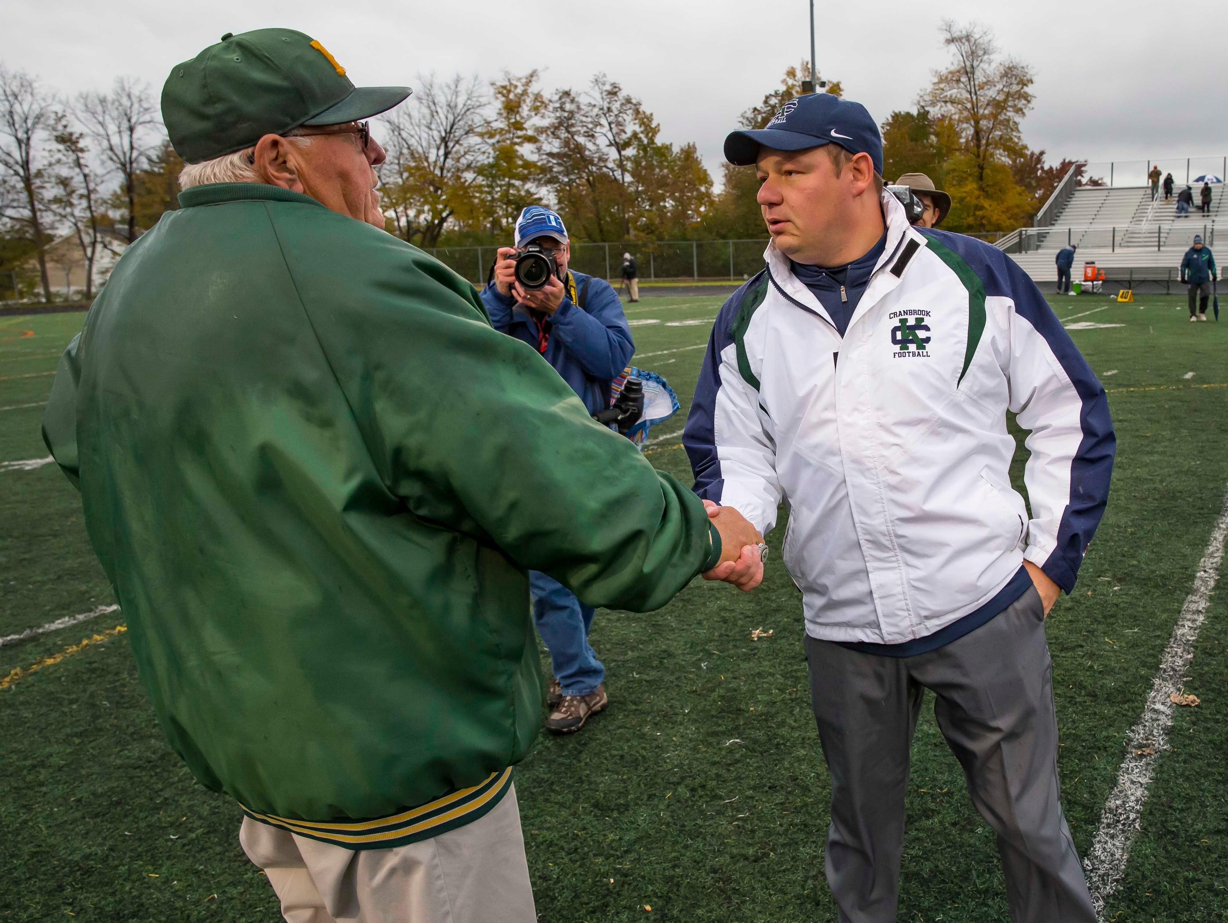 Farmington Hills Harrison head coach John Herrington (left) shakes hands with  head coach Scott Steward of Cranbrook Kingswood after the game.