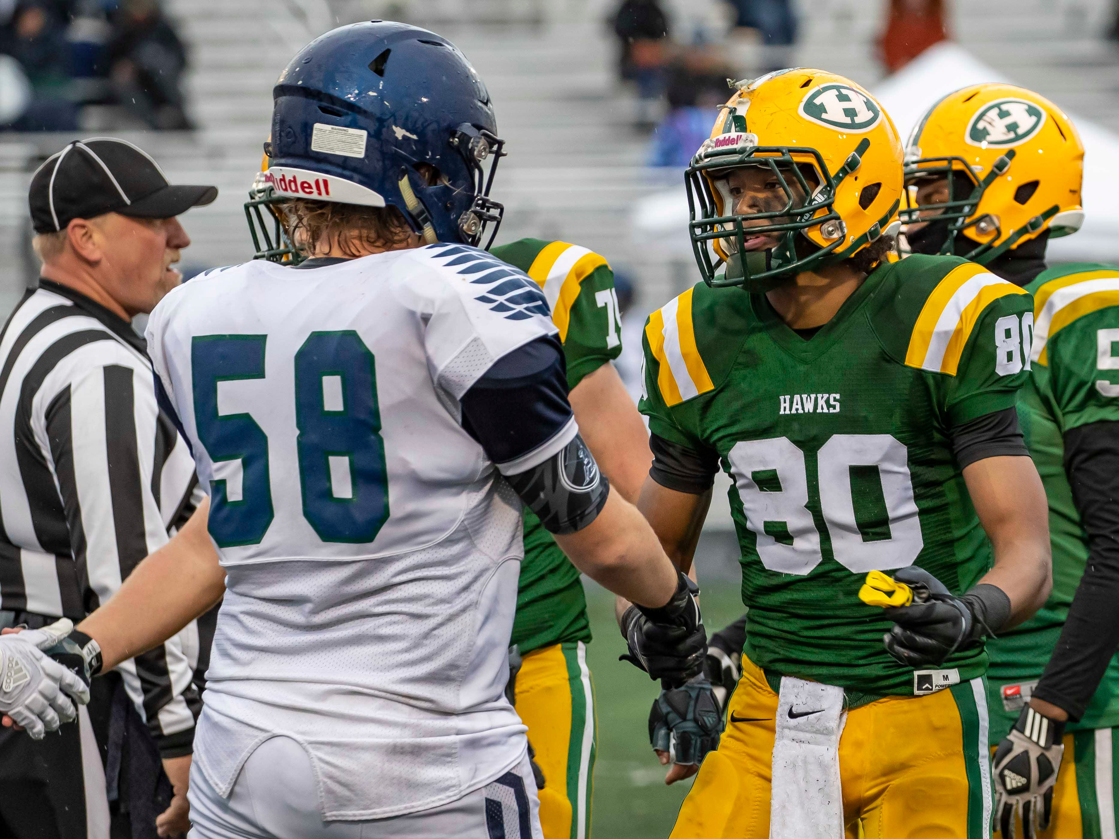 Trenton Ramsey (80) of Farmington Hills Harrison Hawks shakes hands with William Kerr (58) of Cranbrook Kingswood after Harrison's 24-10 playoff victory.