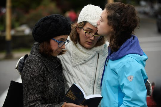 Tammy Hepps, Kate Rothstein and her daughter, Simone Rothstein, 16, pray from a prayerbook a block away from the site of a mass shooting at the Tree of Life Synagogue in the Squirrel Hill neighborhood on Saturday in Pittsburgh.