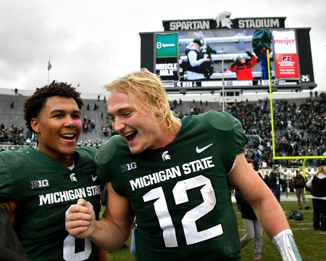 Spartans Rocky Lombardi, right, and Jalen Nailor celebrate at midfield after MSU beat Purdue, 23-13, on Saturday, Oct. 27, 2018 at Spartan Stadium in East Lansing.