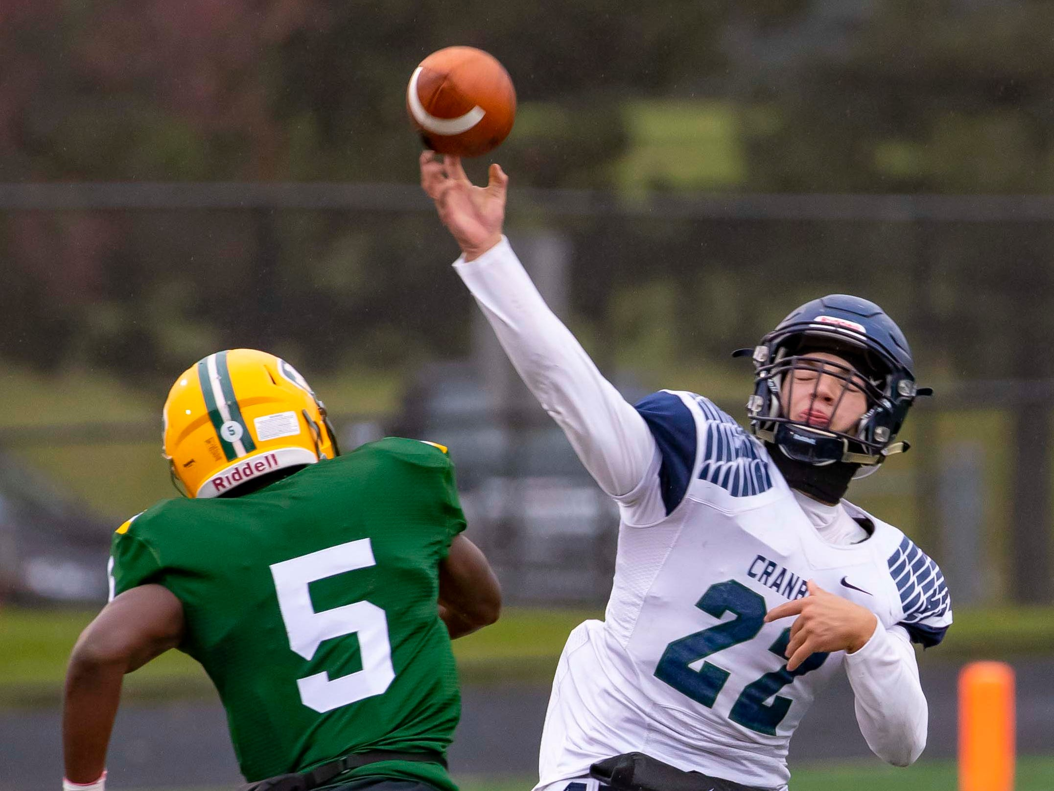 Jack Fairman (22) of Cranbrook Kingswood throws the football as Michael Alford (5) of Farmington Hills Harrison pressures in the first half.