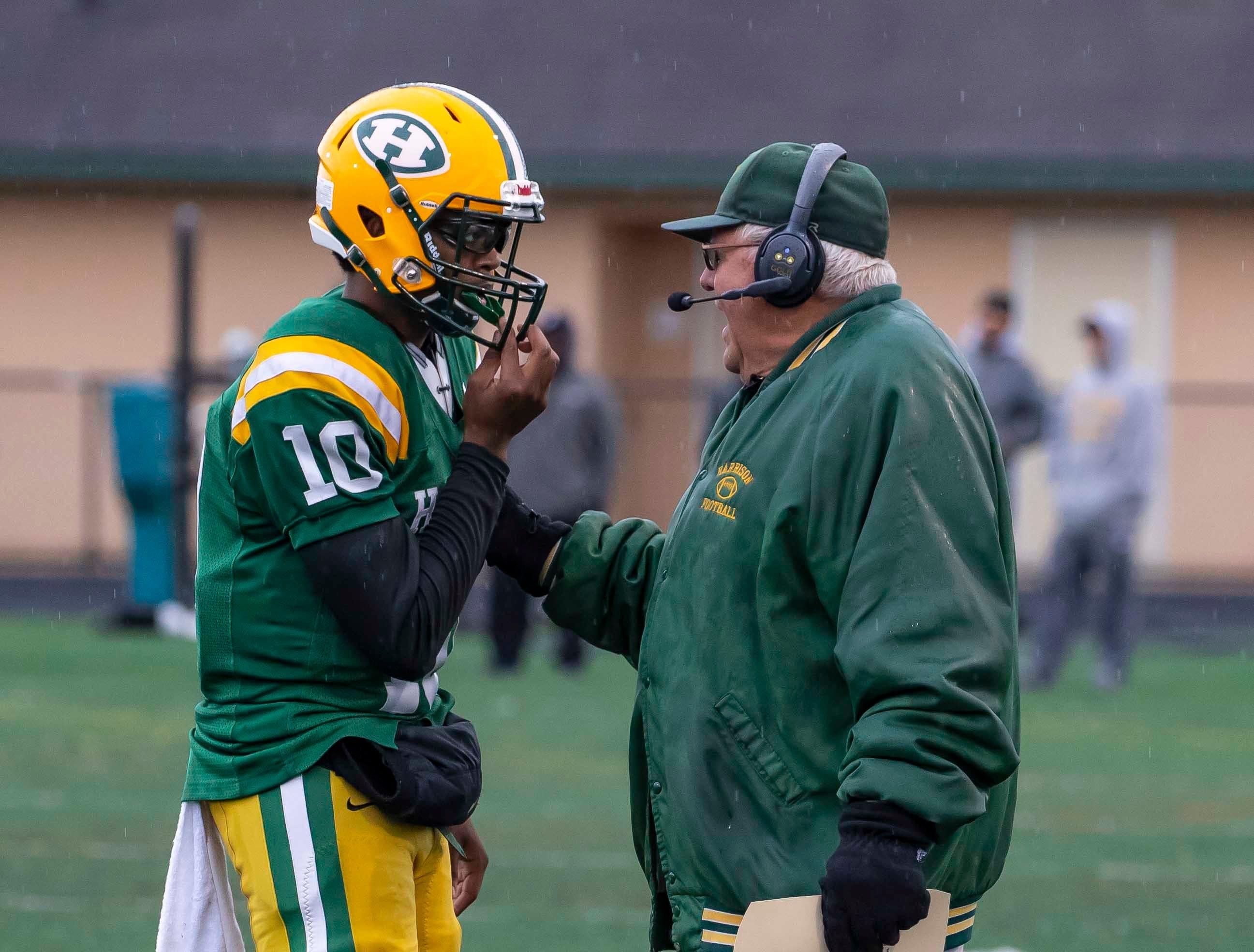 Harrison head coach John Herrington talks to his quarterback Keel Watson (10) in the second half.