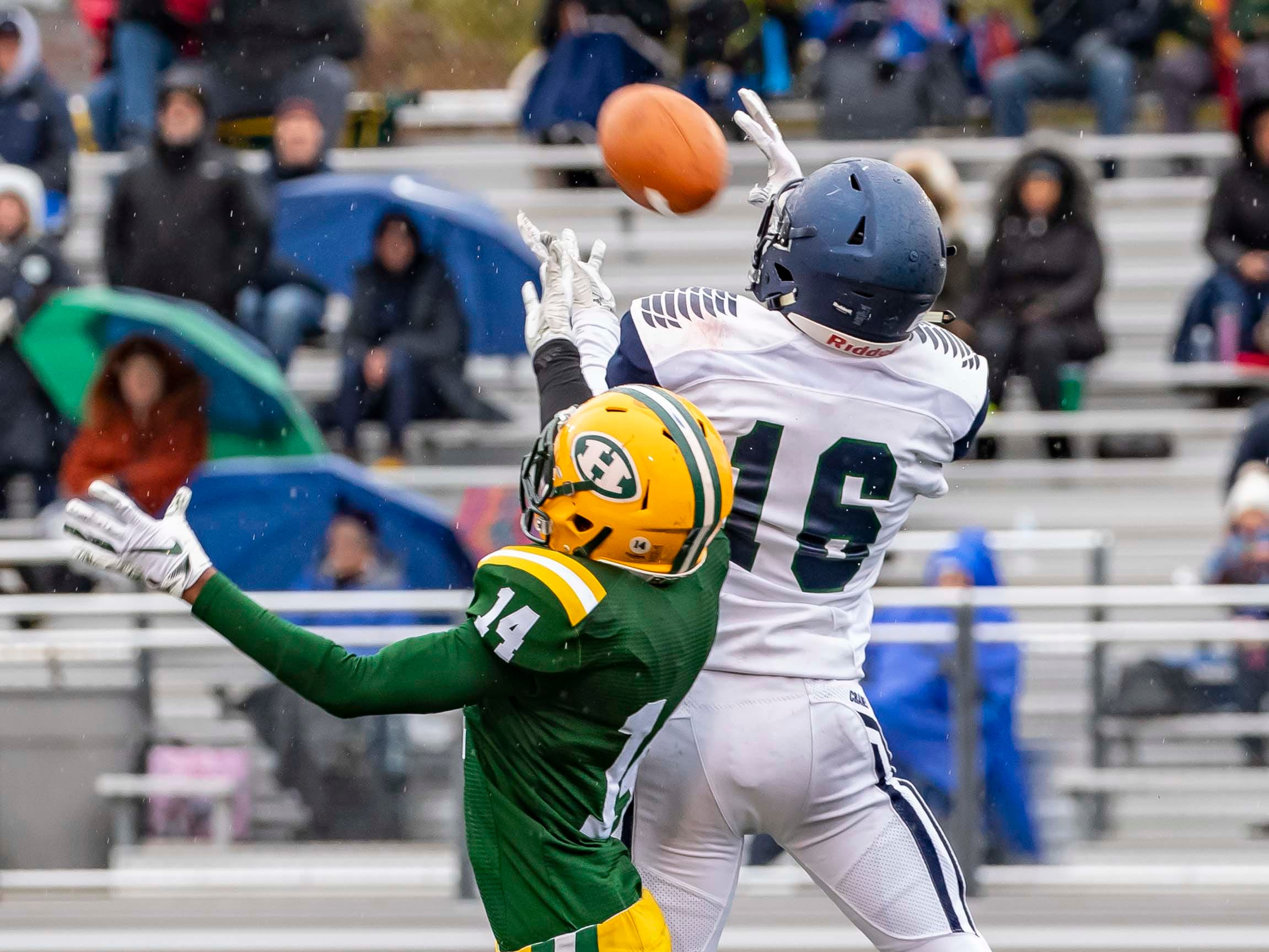 Jacob Peruski (16) of Cranbrook Kingswood attempts to catch a pass as Javair Beeler (14) of Farmington Hills Harrison Hawks defends in the second half.