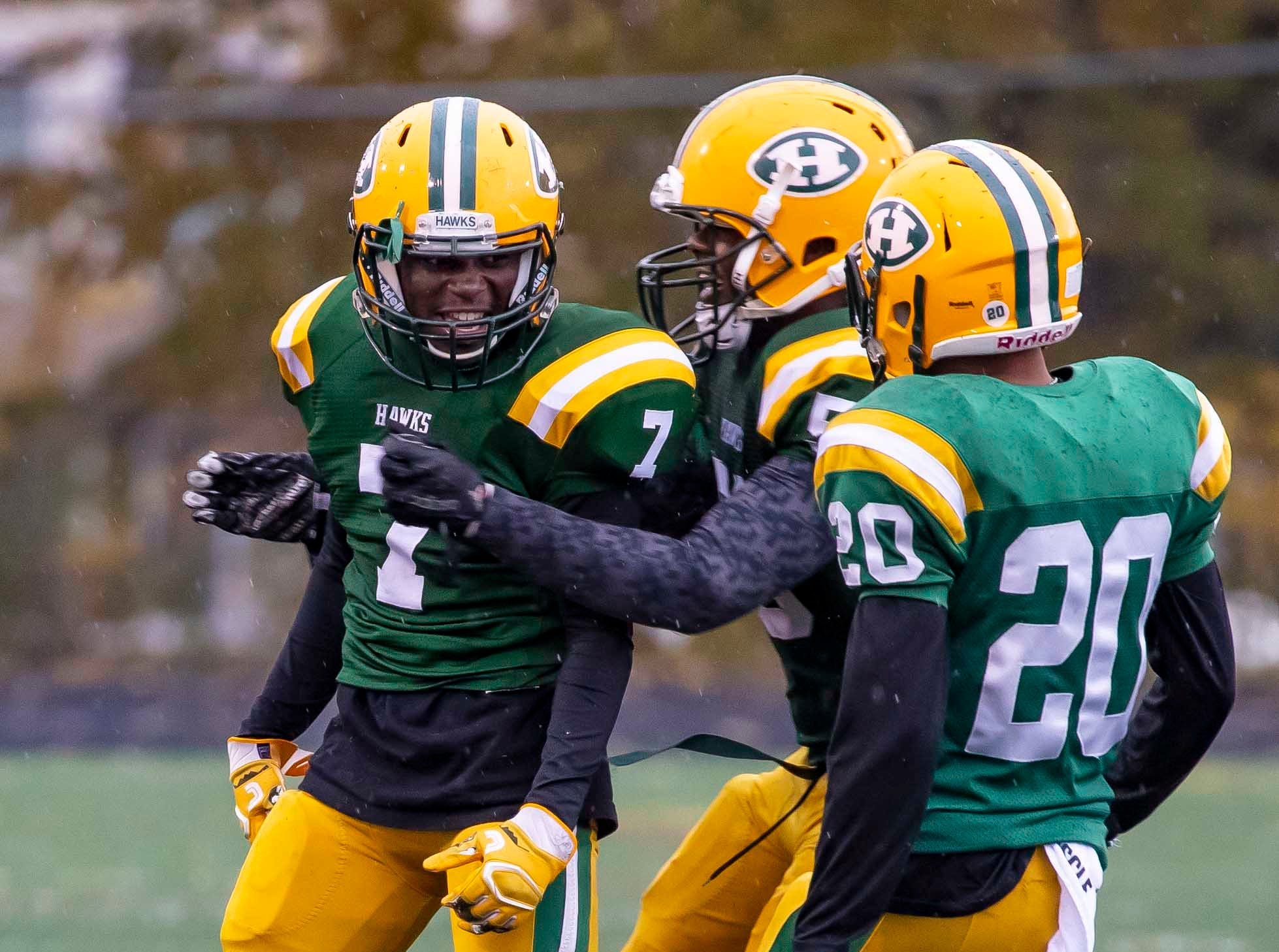 Delwuan Gaston (7) of Farmington Hills Harrison celebrates a sack in the second half against Cranbrook Kingswood with teammates Michael Alford (5) and Xavier Goldsmith (20).