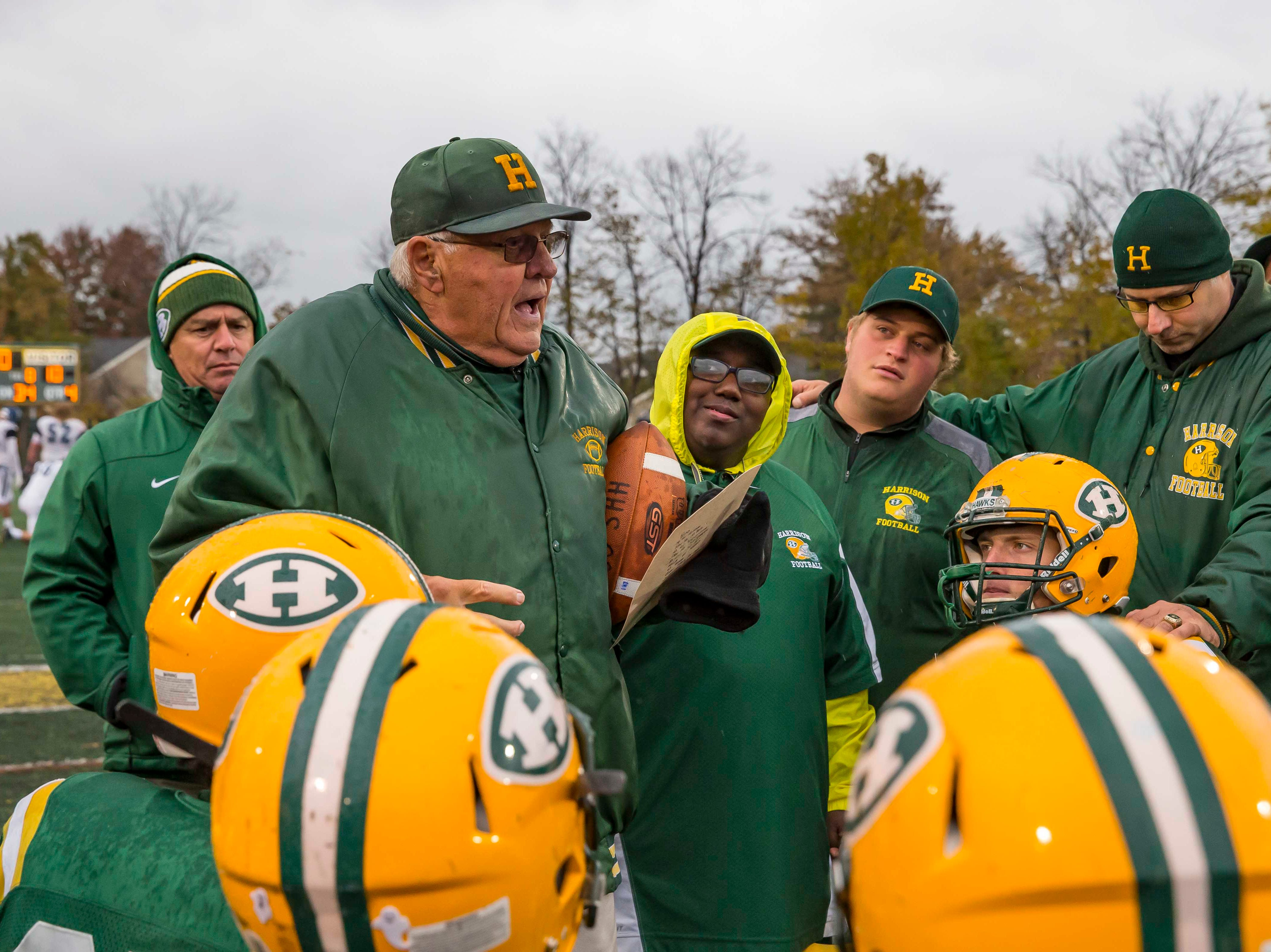Head coach John Herrington of Farmington Hills Harrison talks to his team after they defeated Cranbrook Kingswood 24-10 at the John Herrington Athletic Complex at Buller Field in Farmington Hills, Michigan.