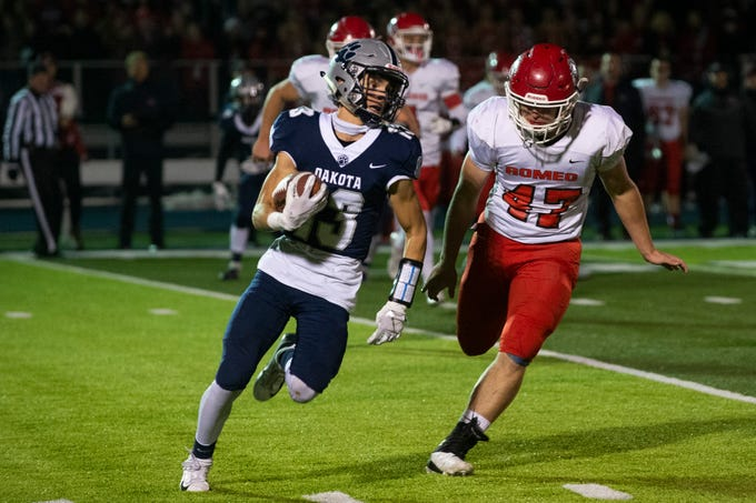Dakota's Patrick Merolla moves with the ball as he is chased by Romeo's Bryce Tinson during the 1st quarter of the Romeo vs. Dakota playoff game on Friday, Oct. 26, 2018 at Dakota High School in Macomb.