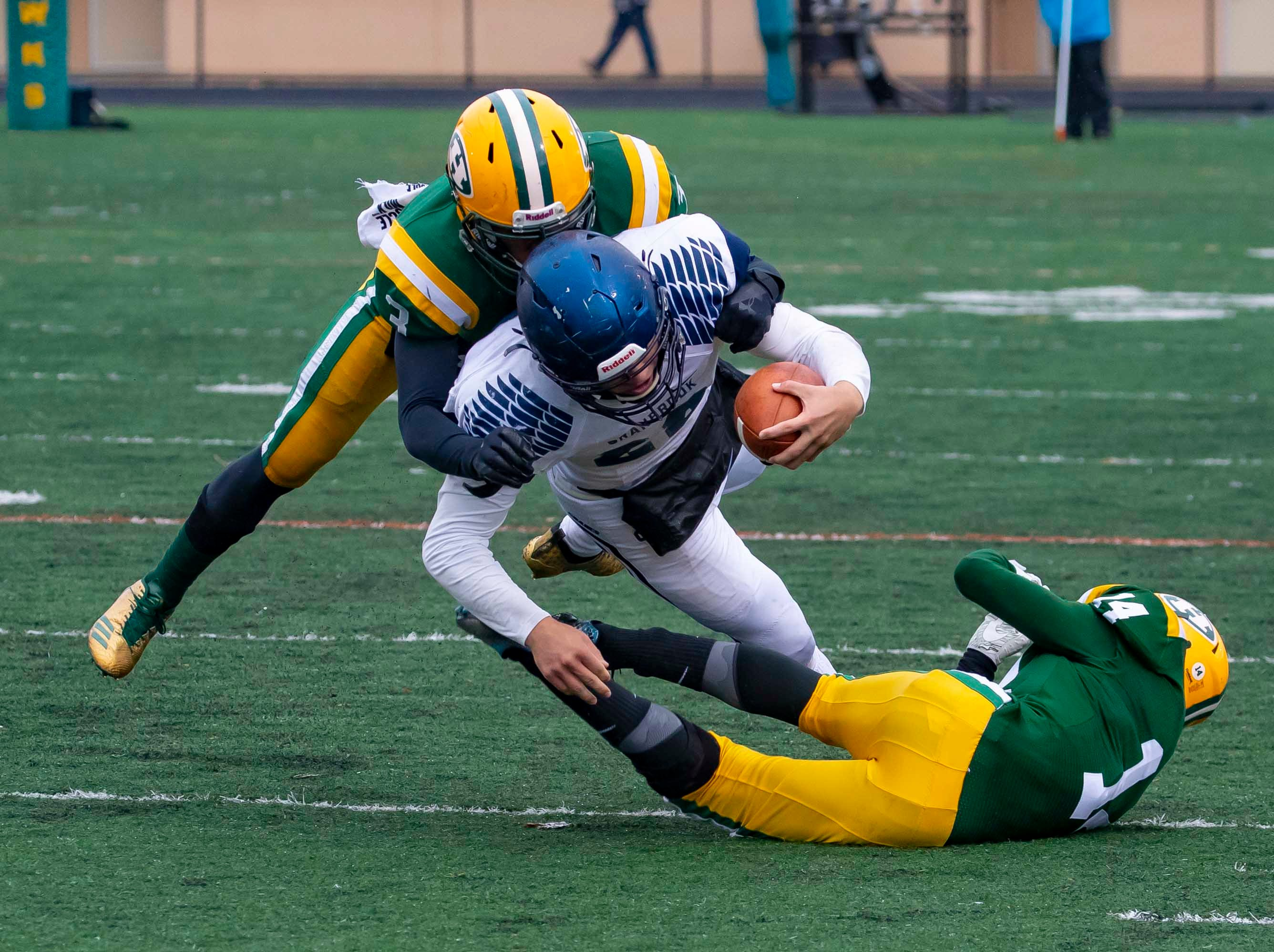 FARMINGTON HILLS, MI - OCTOBER 27: Jack Fairman (22) of Cranbrook Kingswood is tackles by Roderick Heard (3) and Javair Beeler (14) of Farmington Hills Harrison Hawks during a high school football game at John Herrington Athletic Complex at Buller Field on October 27, 2018 in Farmington Hills, Michigan. (Photo by Dave Reginek Special to Detroit News) *** Local Caption ***
