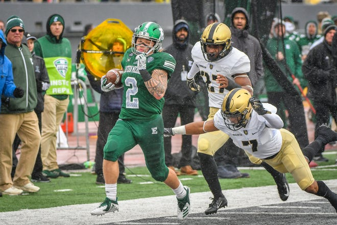 Eastern Michigan  running back Blake Banham runs past Army defenders in Saturday's game at Rynearson Stadium.