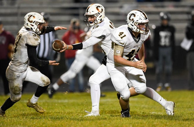 Central quarterback Brennon Harper (13) hands off to teammate Brennan Schutte (38) as the Evansville Central Bears play the Northview Knights in the Class 4A sectional semifinal at Brazil, In. Friday, October 26, 2018.