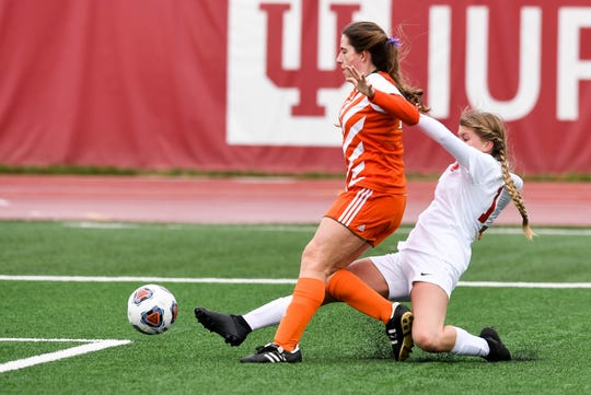Mater Dei's Madde Folz (14) shoots the winning goal past defense from Wheeler's Amber Handley (17) as the defending state champions Mater Dei Wildcats play the Wheeler Bearcats in the Class 1A state championship game in Indianapolis Saturday, October 27, 2018.