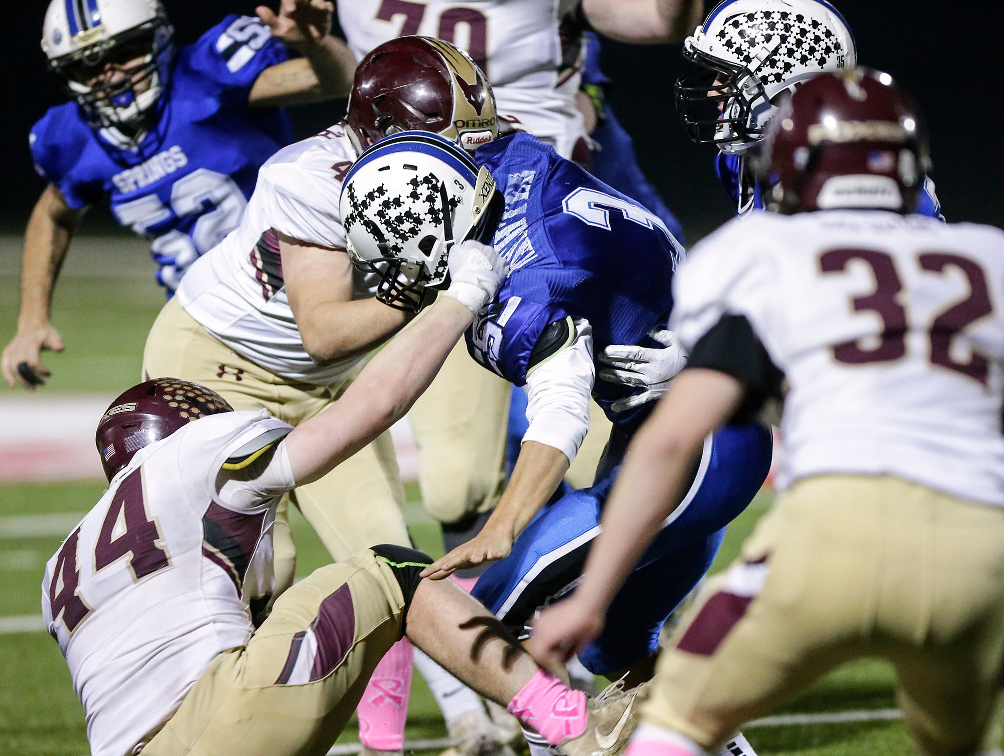 St. Mary's Springs Academy football's Mitchell Waechter gets tackled by Omro High School's Zac Boese (44) and Clayton Markech (42) Friday, October 26, 2018 during their WIAA division five, level 2 playoff game played in Lomira, Wisconsin. Springs won the match-up 33-20. Doug Raflik/USA TODAY NETWORK-Wisconsin