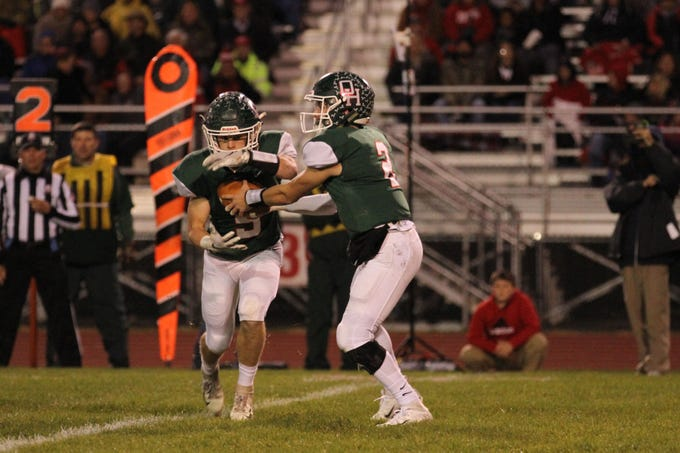 Oak Harbor's Jac Alexander hands the ball off to Clay Schulte against Port Clinton.