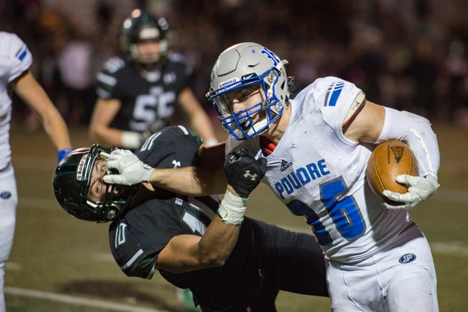 Poudre High School running back Tate Satterfield pushes Fossil Ridge linebacker Tanner Arkin away as he runs the ball in a game at French Field on Friday, October 26, 2018.