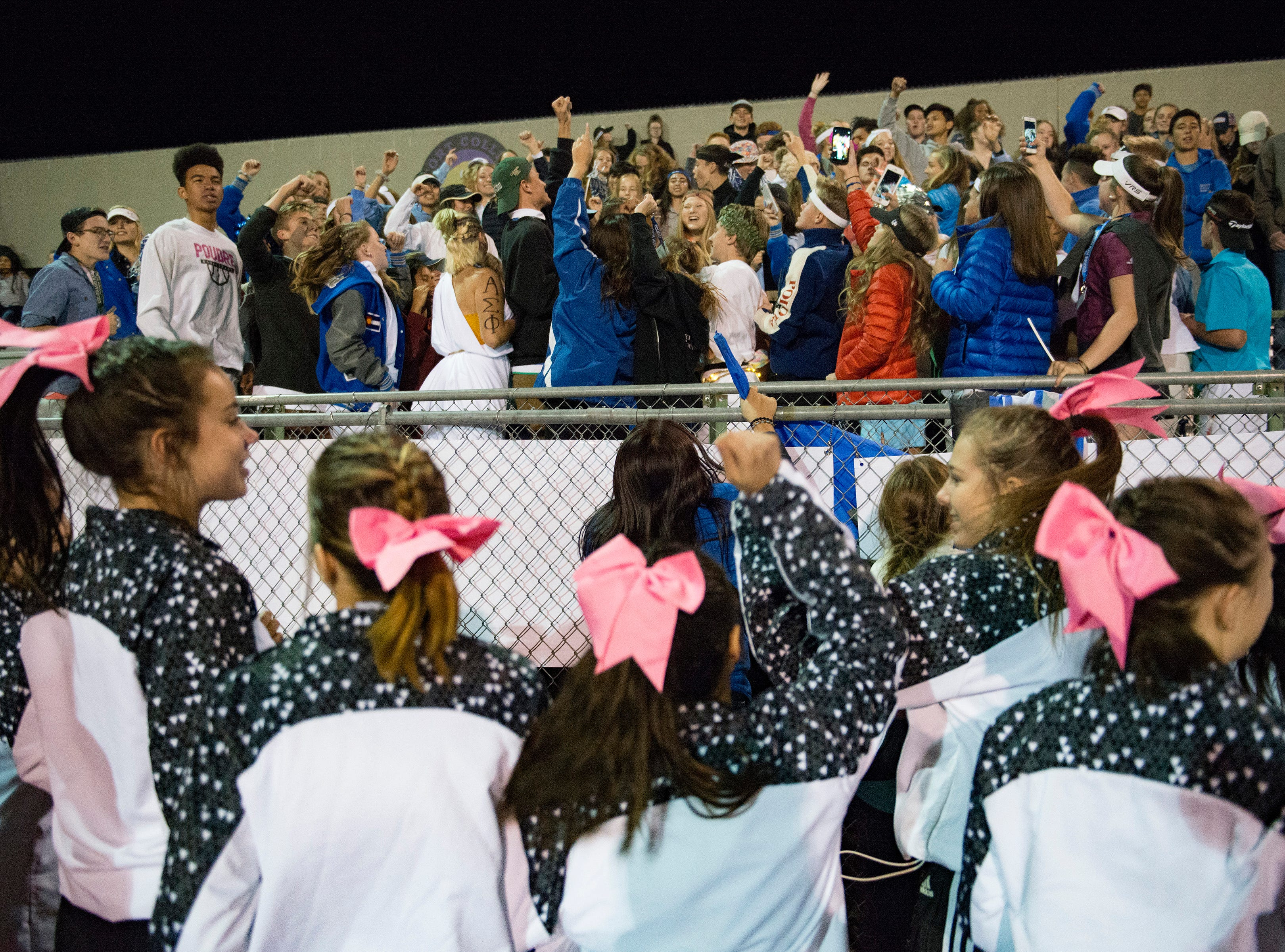 Poudre High School cheerleaders pump up the crowd during a football game against Fossil Ridge at French Field on Friday, October 26, 2018.