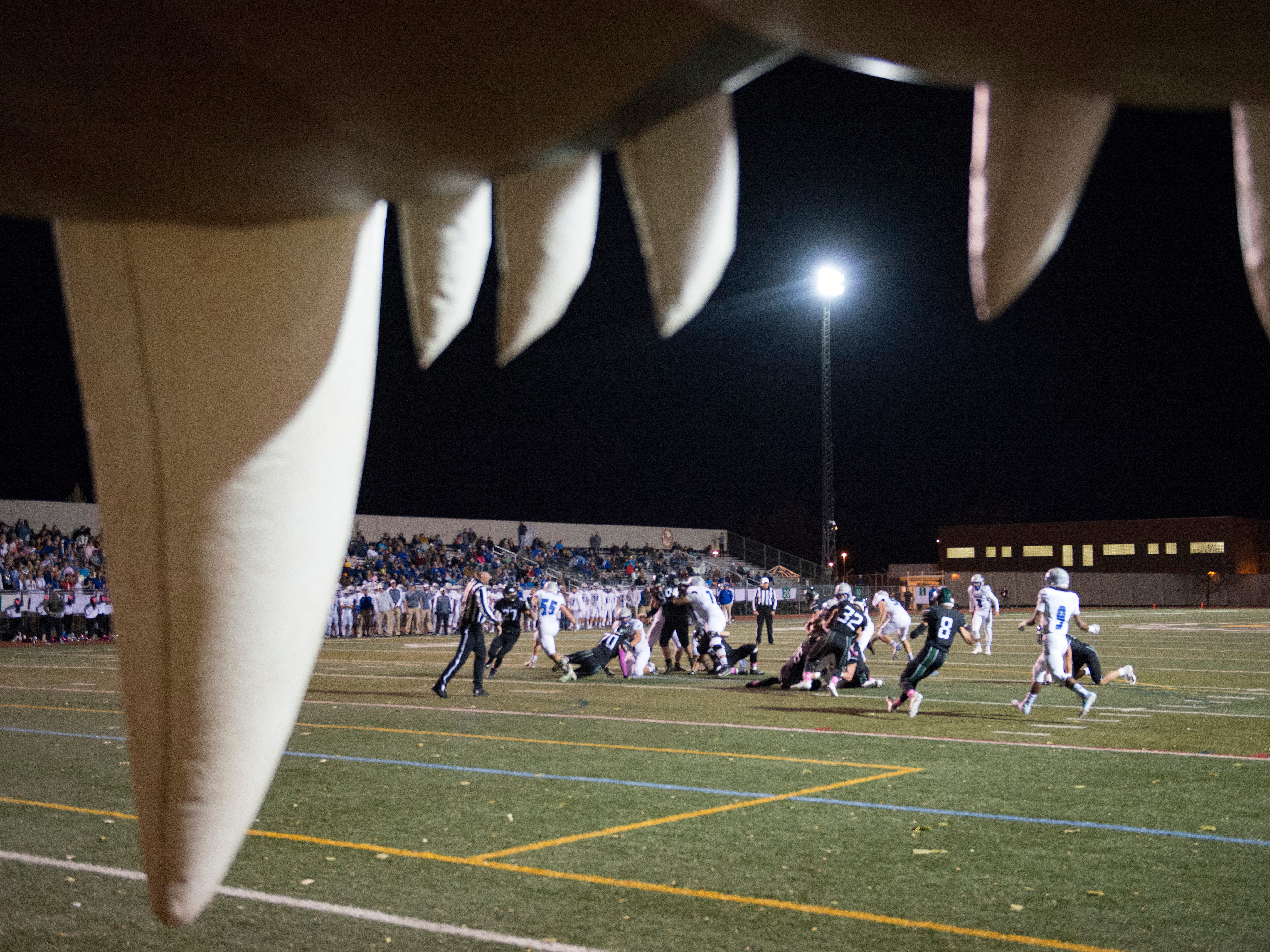 Fossil Ridge and Poudre High School run a play seen through the teeth of the SaberCat during a game at French Field on Friday, October 26, 2018.