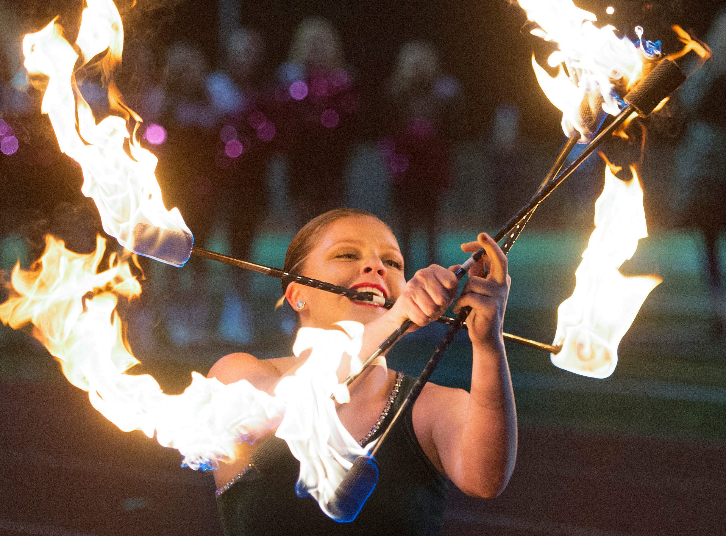 Fossil Ridge baton spinner Katie Harris holds batons on fire during half-time as the SaberCats take on Poudre at French Field on Friday, October 26, 2018.