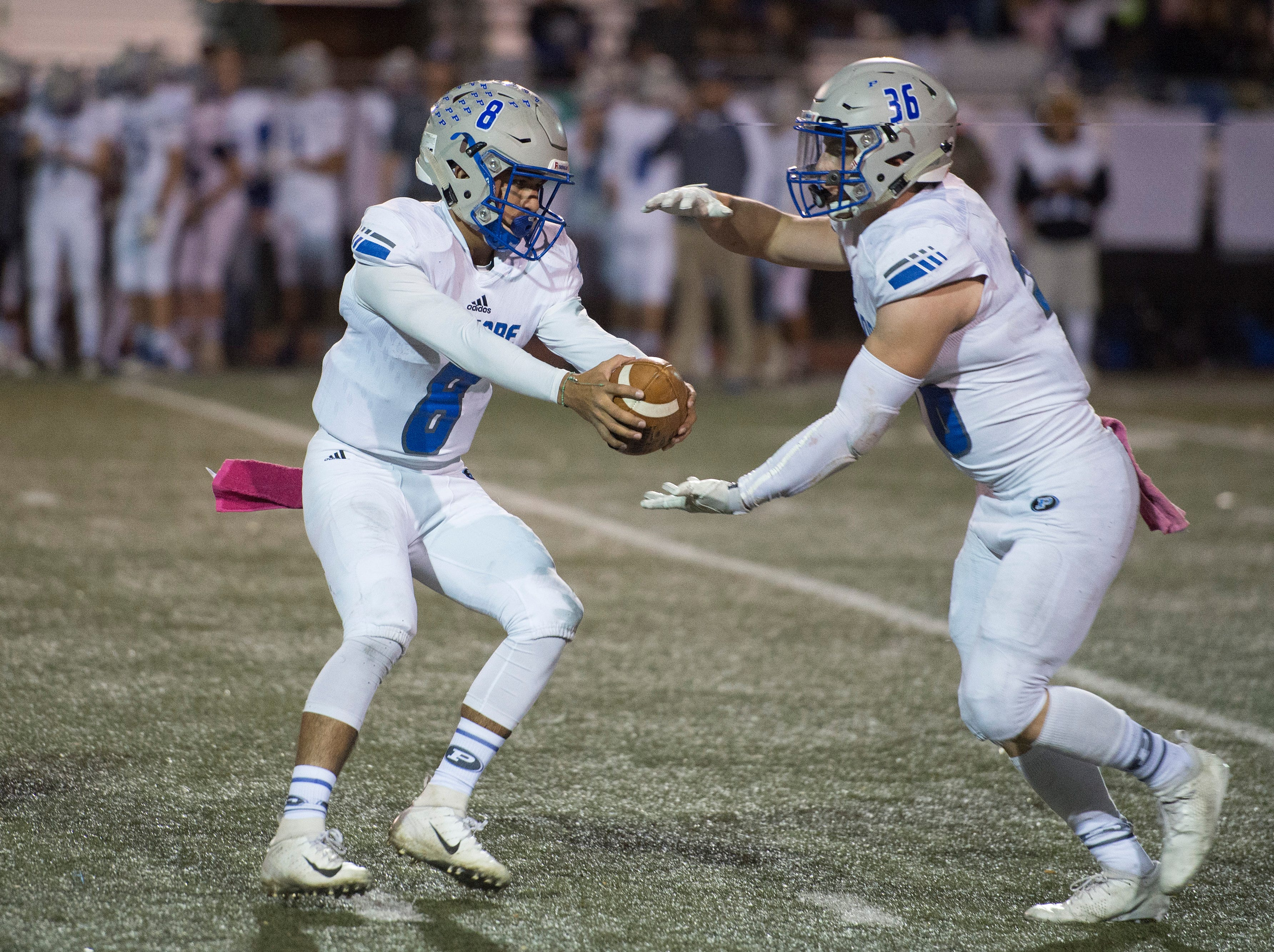 Poudre quarterback Sergio Tarango fakes a hand-off to running back Tate Satterfield during a game against Fossil Ridge at French Field on Friday, October 26, 2018.