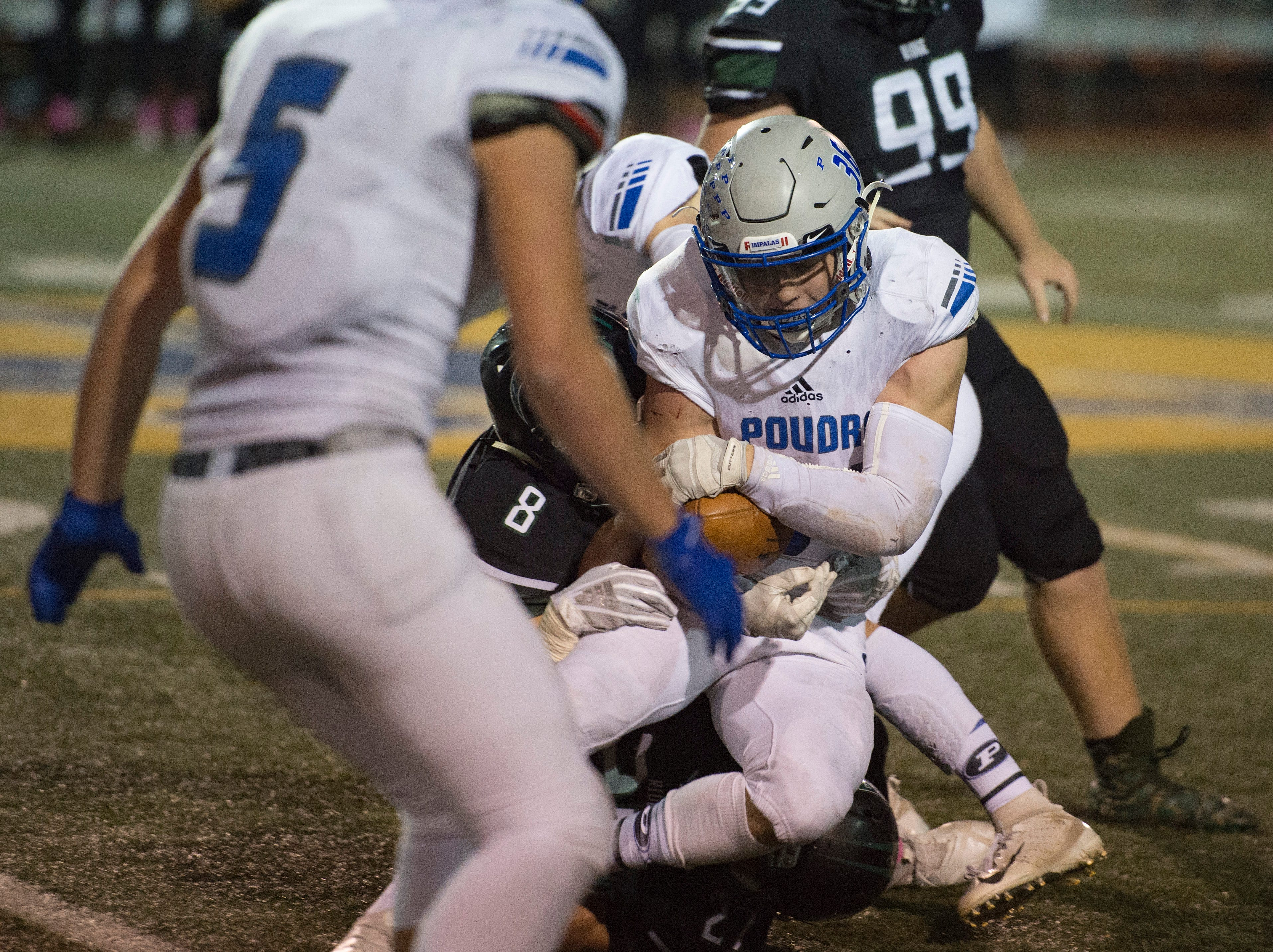 Poudre High School running back Tate Satterfield is brought down by  Fossil Ridge's Ryan Ressler in a game at French Field on Friday, October 26, 2018.