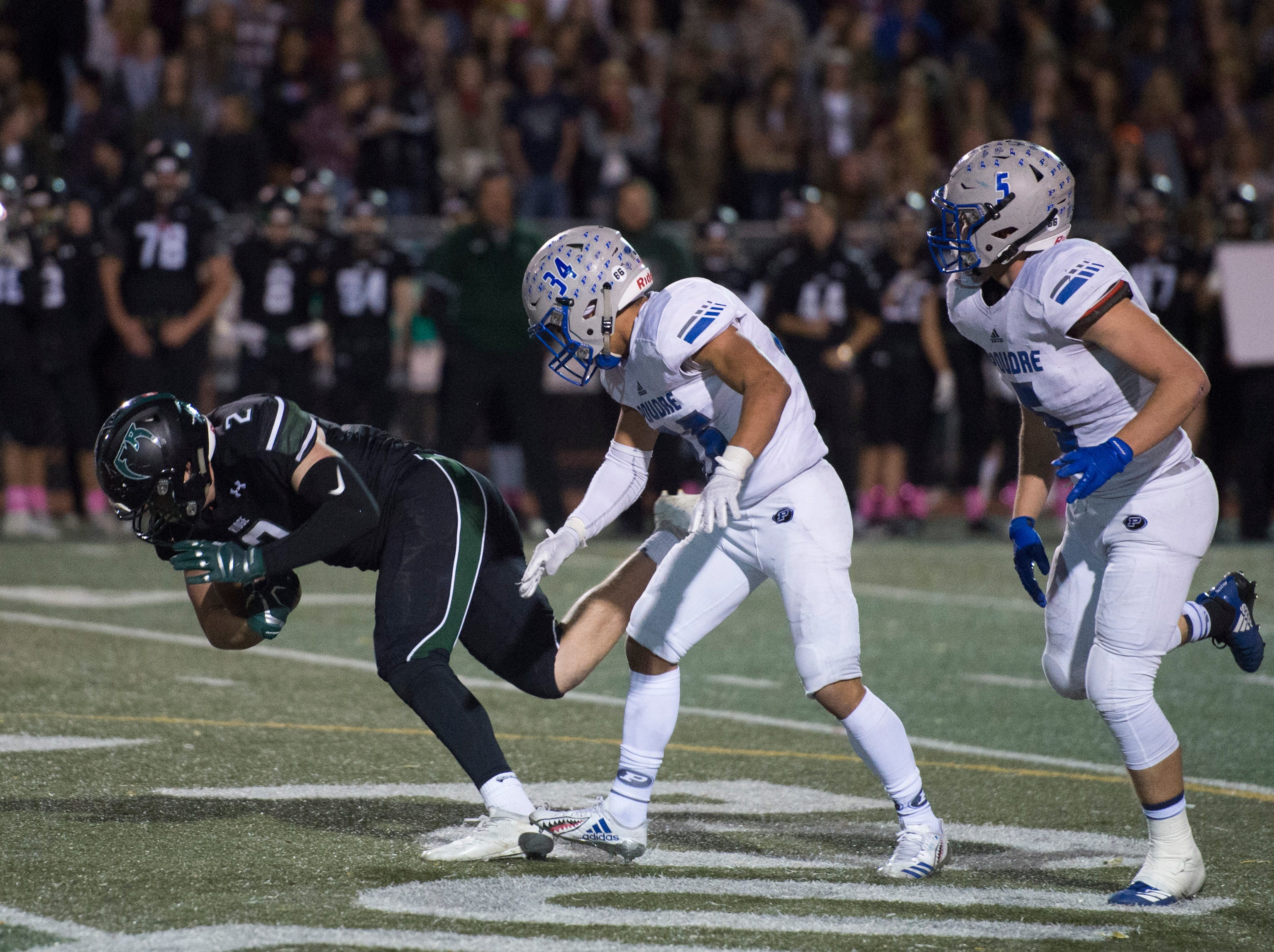 Fossil Ridge High School's Jack Blomfelt goes down after a push from defensive back Kobi Salinas during a game against Poudre at French Field on Friday, October 26, 2018.